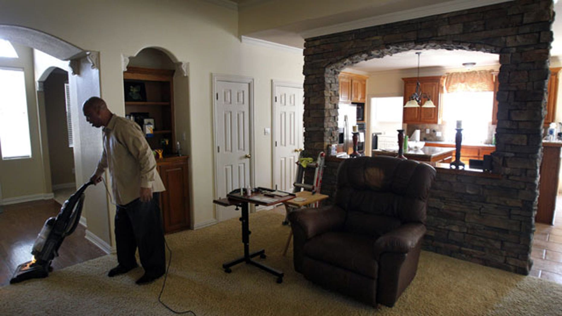 In this photo taken Wednesday, July 27, 2011, Kenneth Robinson vacuums the spacious living room of the home in Flower Mound, Texas.