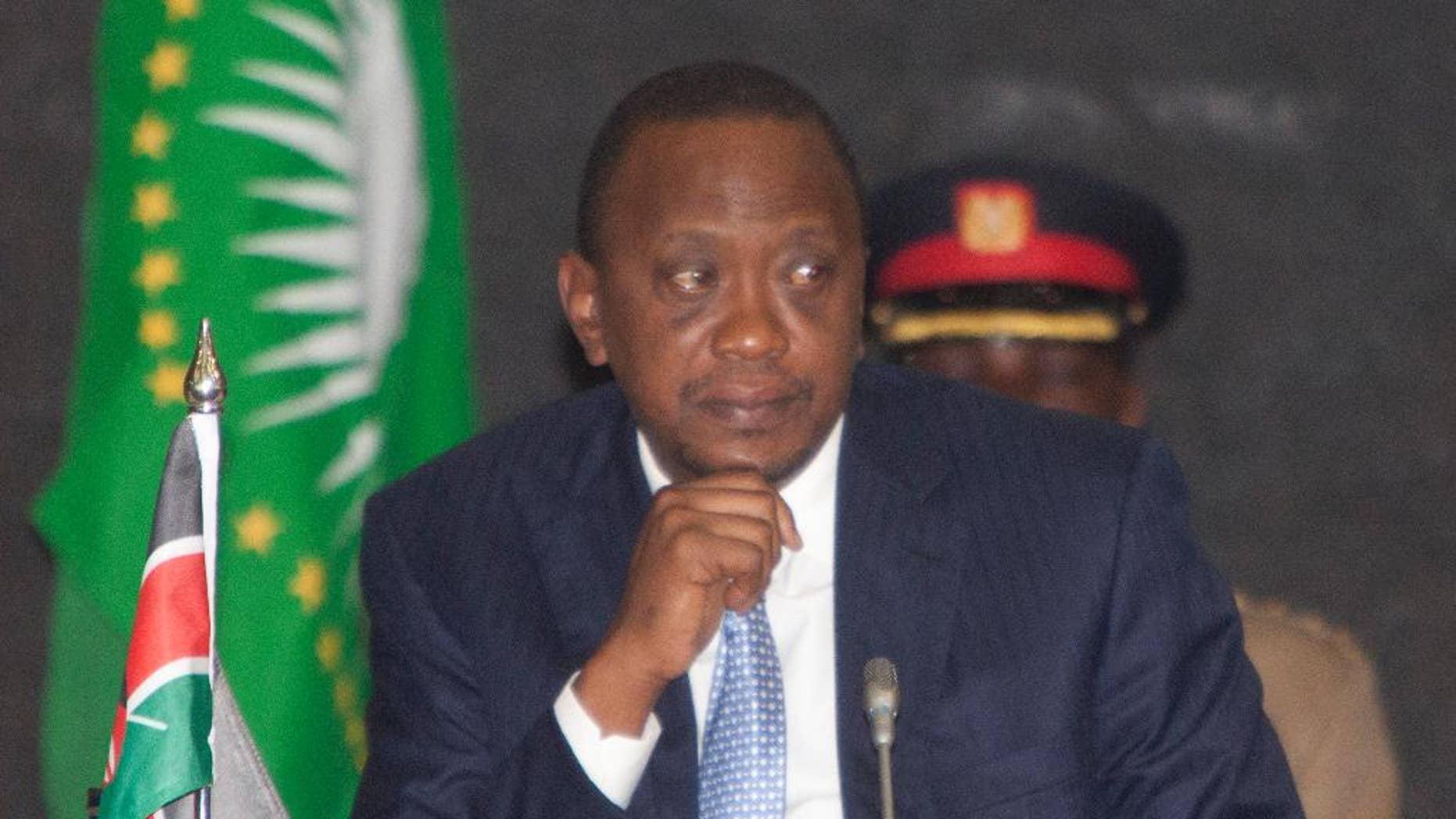 President of Kenya, Uhuru Kenyatta, listens during the AU Summit, Tuesday, Sept. 2, 2014, in Nairobi, Kenya.  A one-day African Union Peace and Security Summit  started in Nairobi, Kenya, Tuesday. (AP Photo/Sayyid Azim)