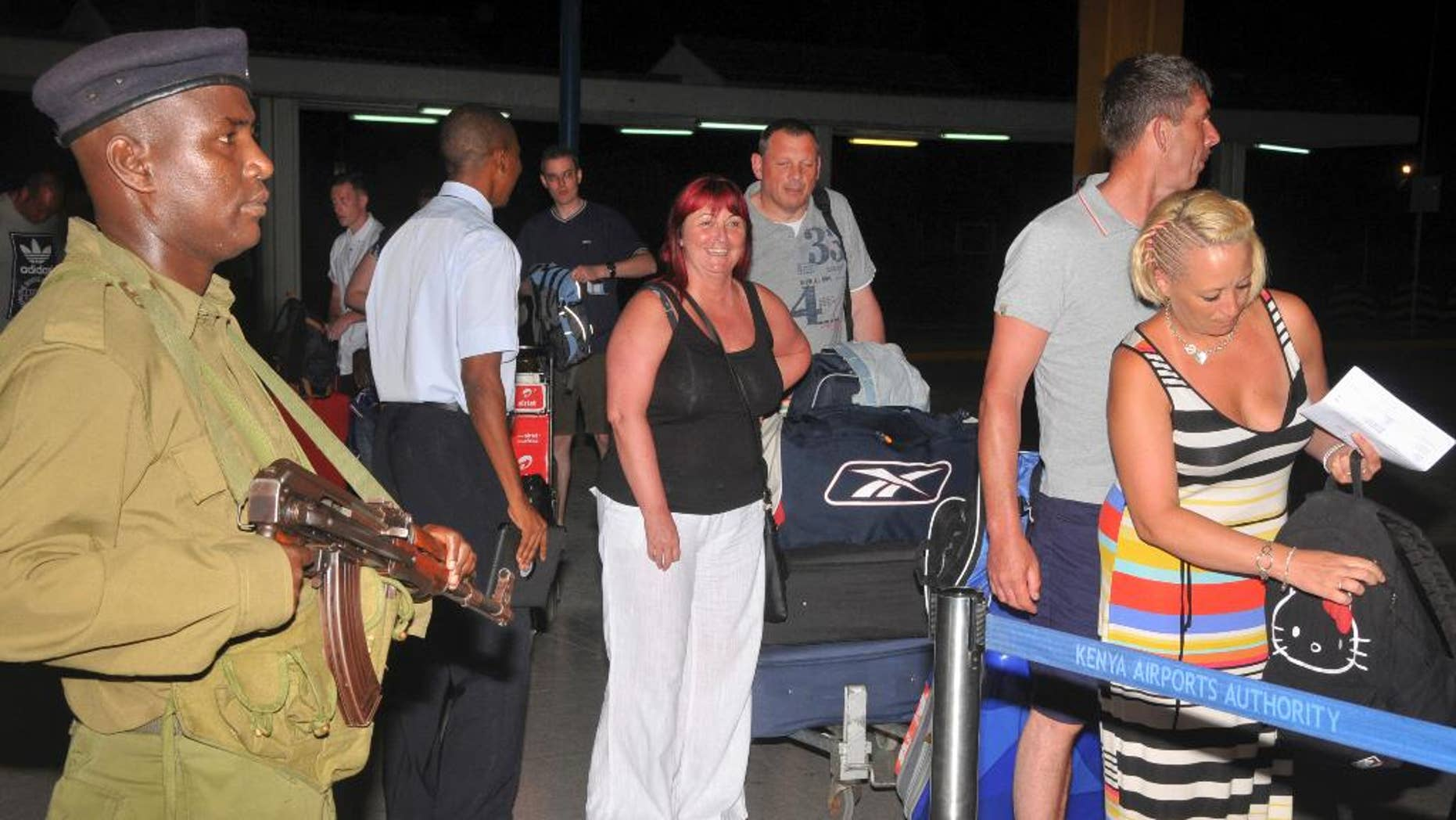 In this photo taken late Thursday, May 15, 2014, British tourists queue to prepare to leave the international airport in Mombasa, Kenya. A number of British tourists left the country by charter flight Thursday following a new travel advisory from the British Foreign and Commonwealth Office (FCO) advising against all but essential travel to Mombasa island. (AP Photo)