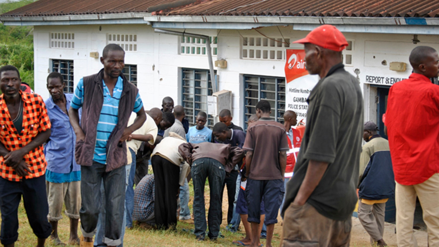 July 6, 2014: People watch the site where gunmen attacked outside the Gamba police station in Gamba, Kenya. (AP Photo)