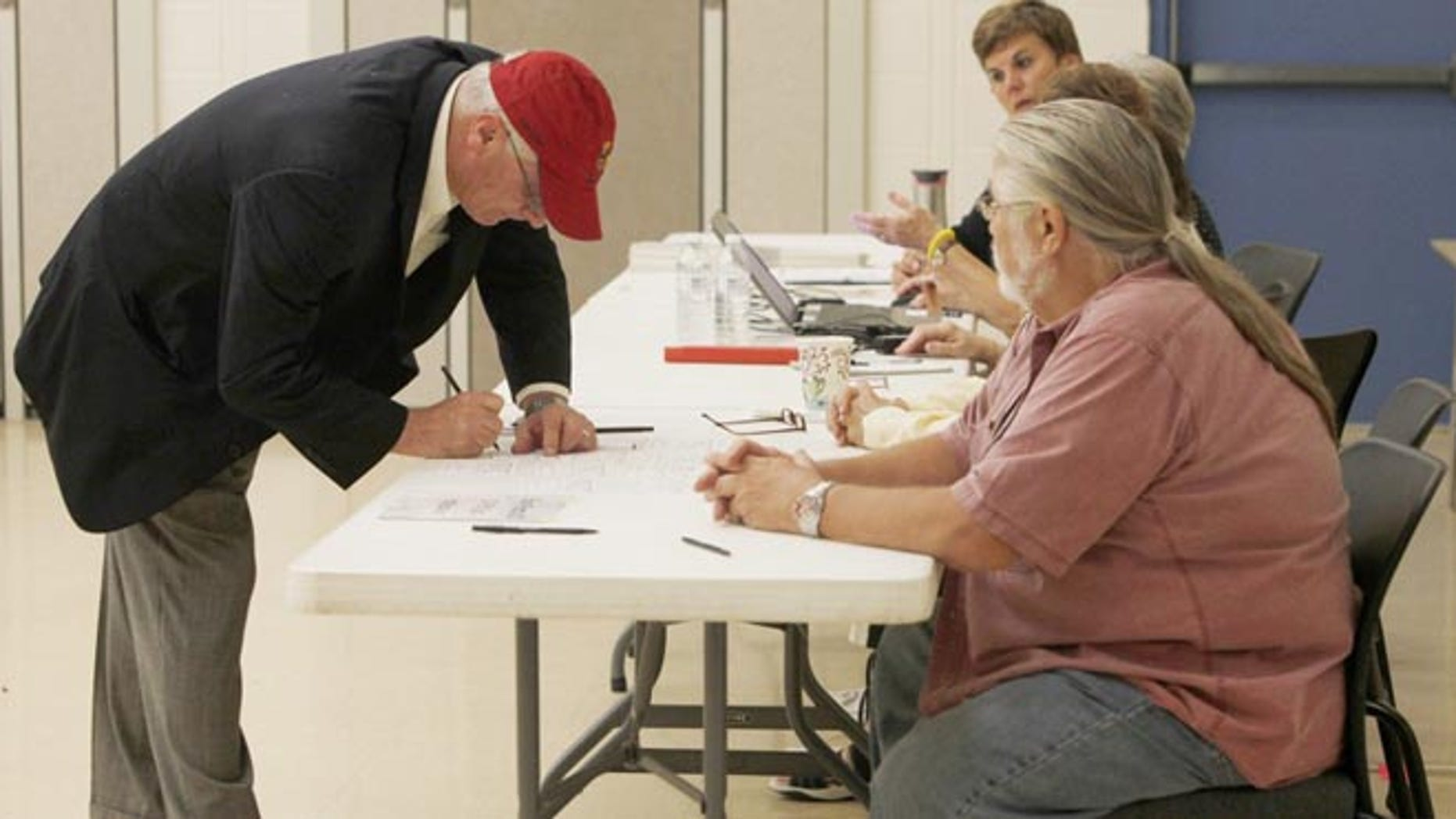 Aug. 5, 2014: Rep. Kerry Bentivolio signs in to vote at Johnson Elementary School in Milford, Mich.