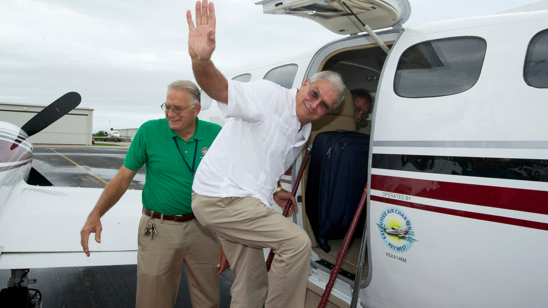 In this photo provided by the Florida Keys News Bureau, Key West Mayor Craig Cates, right, waves goodbye as he boards a chartered aircraft at Key West International Airport Monday, Dec. 30, 2013, that flew to Havana, Cuba. The trip was the first legal commercial passenger flight from Key West to Cuba in more than 50 years and carried passengers who will remain until Jan. 3, 2014. It was organized by the Florida Keys Tropical Research Ecological Exchange Institute under a people-to-people cultural exchange license. Cates accompanied the passengers but did not stay in Cuba and returned to Key West. At left is Monroe County Airports Director Peter Horton. (AP Photo/Florida Keys News Bureau)