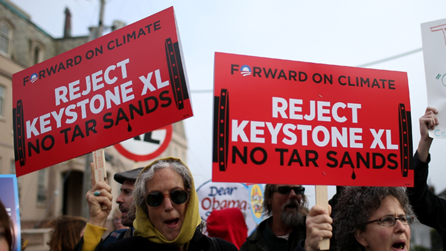SAN FRANCISCO, CA - APRIL 03:  Demonstrators hold signs as they protest near the site of a fundraiser on April 3, 2013 in San Francisco, California.  Hundreds of protesters staged a demonstration against war and the Keystone XL pipeline outside of a fundraiser to be attended by U.S. President Barack Obama at the home of Ann and Gordon Getty. (Photo by Justin Sullivan/Getty Images)