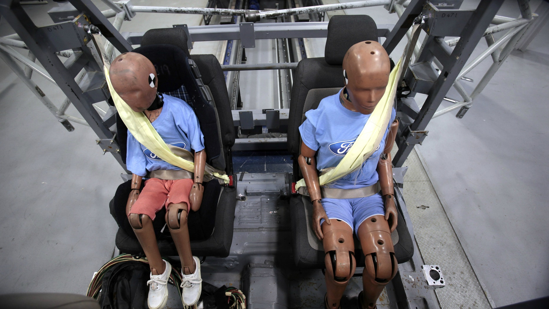 Two Ford Motor Co. crash test dummies sit strapped in a Servo Sled Crash Simulator with seat belt air bags.