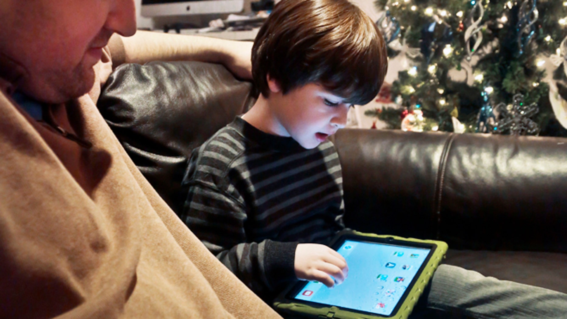 Dec. 3, 2013: Adam Cohen watches as his son Marc, 5, uses a tablet at their home in New York. Tablets of all types are expected to rank among the top holiday gifts for children this year, but some experts and advocates question the educational or developmental benefits for youngsters.