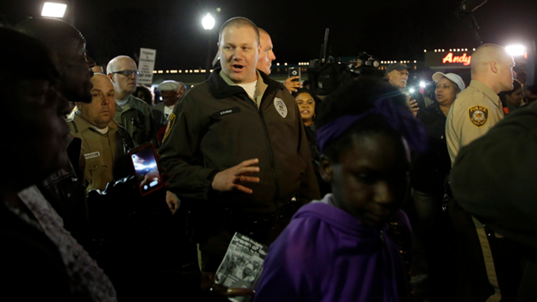 March 12, 2015: Members of the St. Louis County Police Department walk through a crowd of protesters trying to move them out of the street in front of the Ferguson Police Department. (AP Photo/Jeff Roberson)