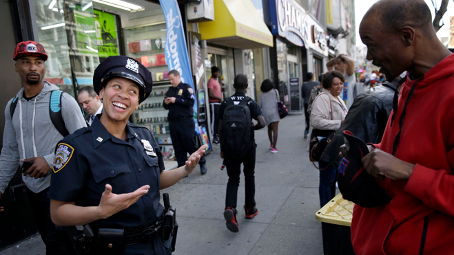 Police officer Lanora Moore talks with a man on 125th Street in the Harlem section of New York, Wednesday, April 29, 2015. (AP Photo/Seth Wenig)