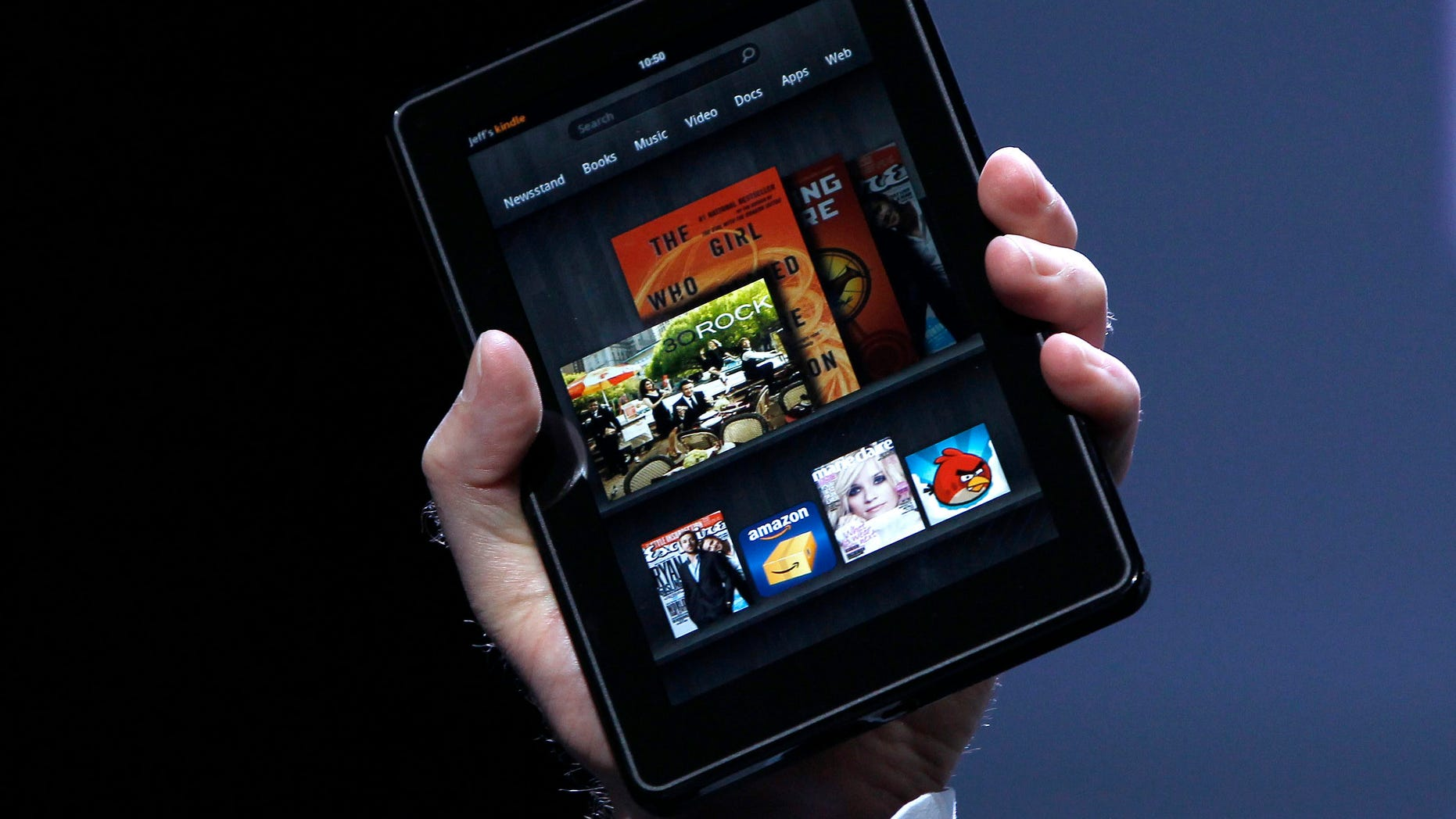 Amazon CEO Jeff Bezos holds up the new Kindle Fire at a news conference during the launch of Amazon's new tablets in New York, September 28, 2011. REUTERS/Shannon Stapleton (UNITED STATES - Tags: BUSINESS SCIENCE TECHNOLOGY) - RTR2RYAH