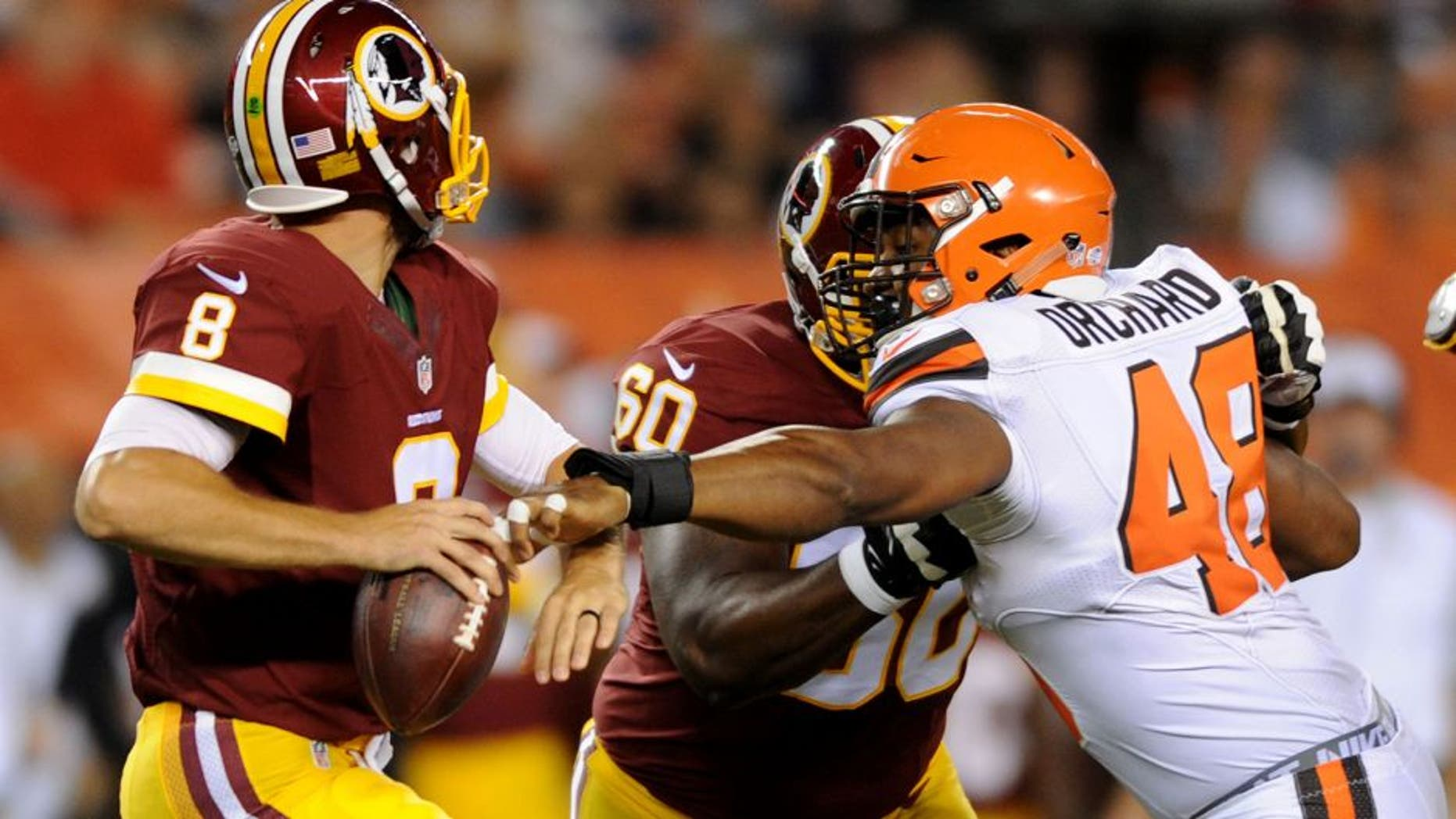 Aug 13, 2015; Cleveland, OH, USA; Cleveland Browns linebacker Nate Orchard (48) gets a hand on Washington Redskins quarterback Kirk Cousins (8) as Washington Redskins tackle Willie Smith (60) blocks during the second quarter in a preseason NFL football game at FirstEnergy Stadium. Mandatory Credit: Ken Blaze-USA TODAY Sports