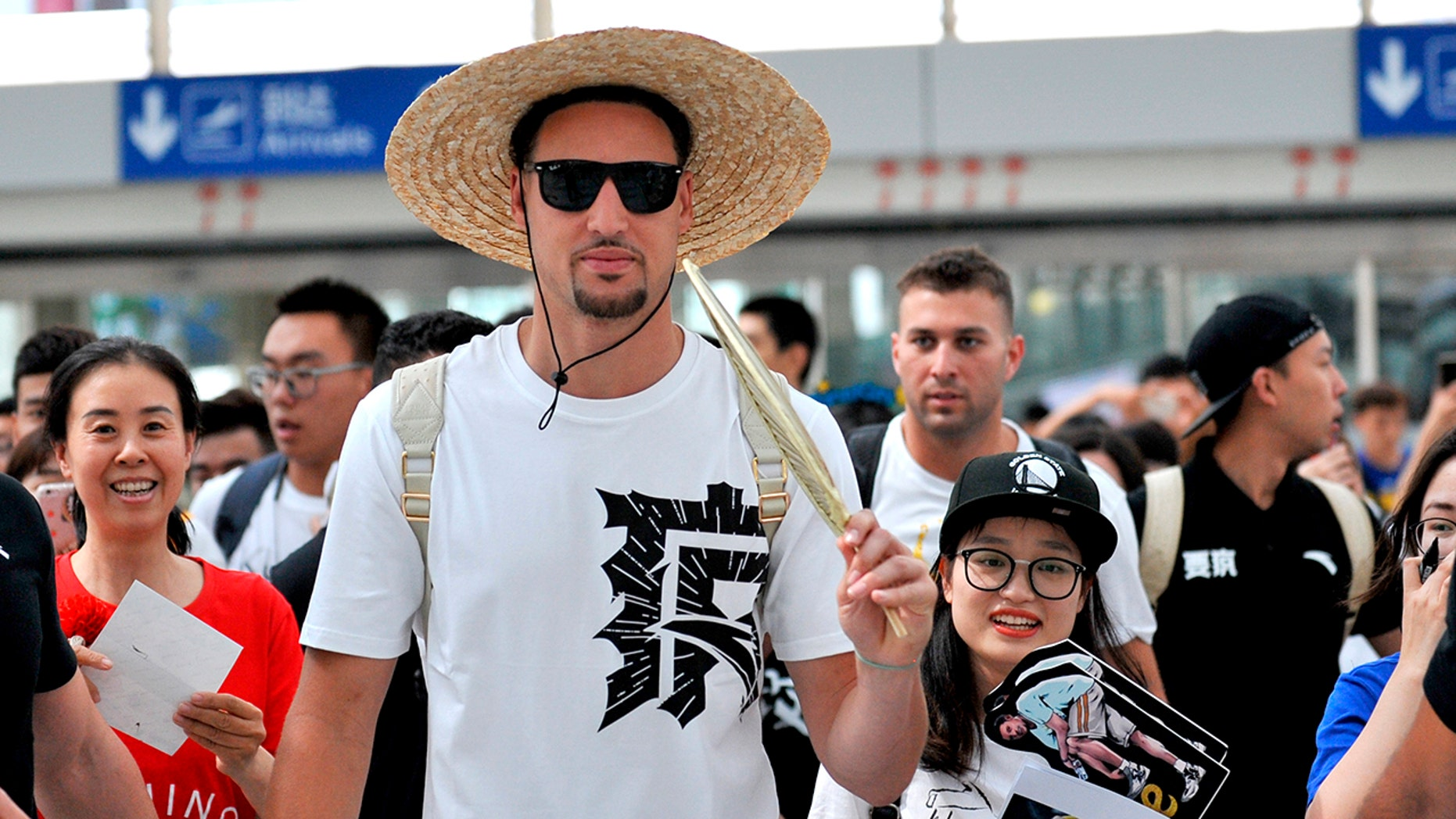 Klay Thompson, with a straw hat on the head, incites a palm-leaf fan as he arrives at the Beijing Capital International Airport in Beijing.