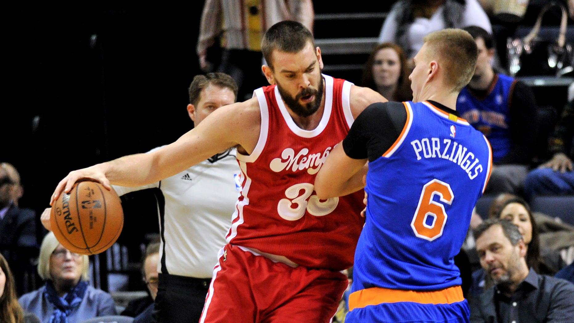 Memphis Grizzlies center Marc Gasol (33) controls the ball against New York Knicks forward Kristaps Porzingis (6) in the first half of an NBA basketball game Saturday, Jan. 16, 2016, in Memphis, Tenn. (AP Photo/Brandon Dill)