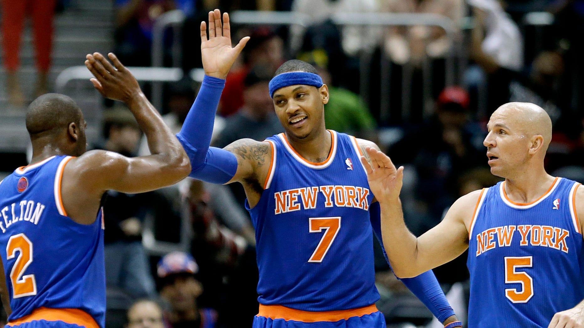 New York Knicks' Carmelo Anthony, center, high-fives teammates Raymond Felton, left, and Jason Kidd after the Knicks beat the Atlanta Hawks 95-82 in an NBA basketball game, Wednesday, April 3, 2013, in Atlanta. (AP Photo/David Goldman)