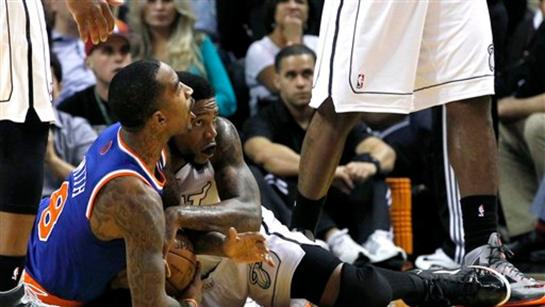 New York Knicks' J.R. Smith (8) battles Miami Heat's Udonis Haslem (40) for control of the loose ball during the first half of an NBA basketball game, Thursday, Dec, 6, 2012, in Miami.