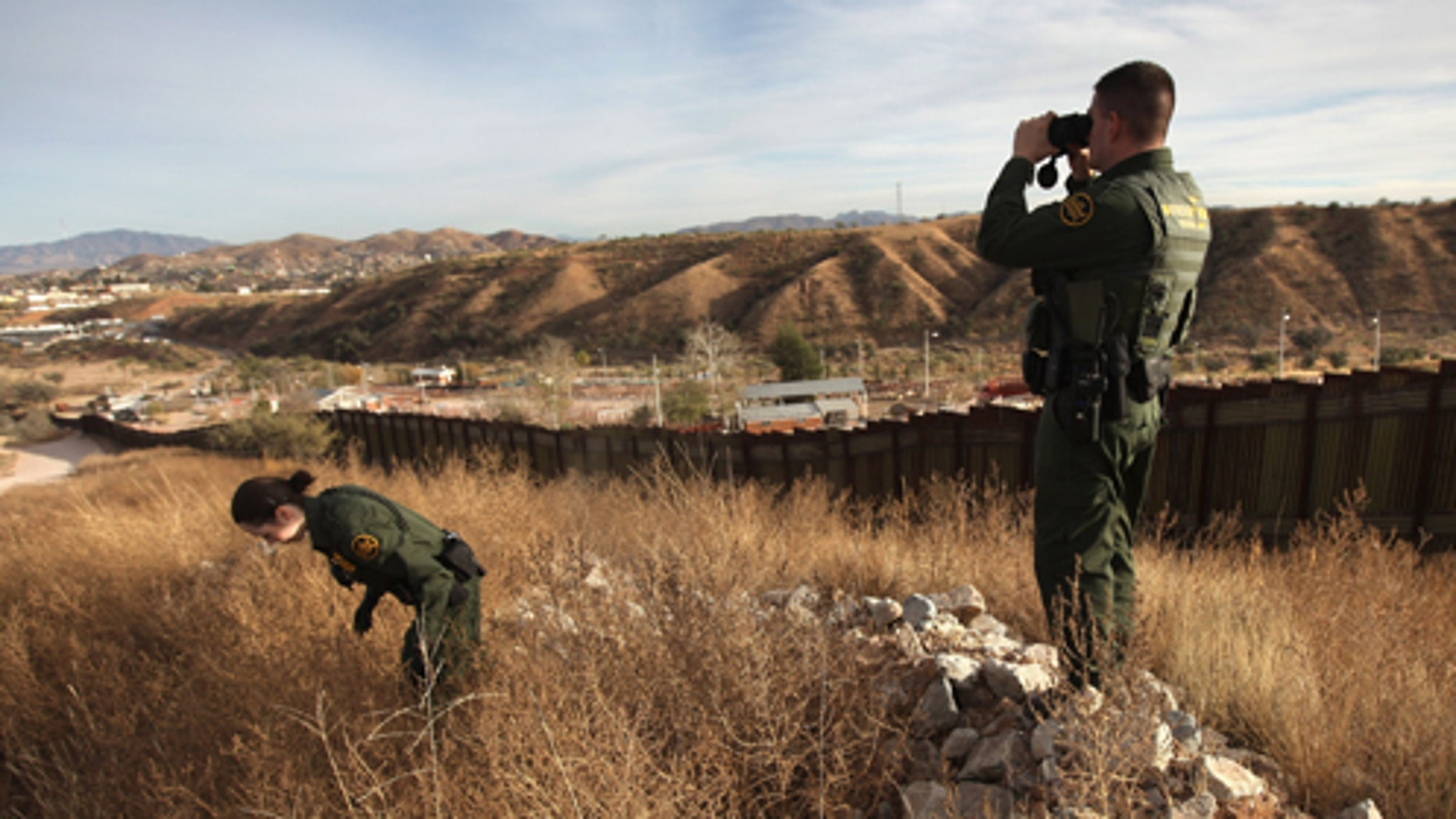 NOGALES, AZ - DECEMBER 07:  U.S. Border Patrol agents Richard Funke and Colleen Agle look for illegal immigrants crossing the U.S.- Mexico border on December 7, 2010 near Nogales, Arizona. Although a new fence has been built along the majority of Arizona's border with Mexico, critics have called for fencing of the entire stretch. Much of the unfenced terrain is in remote and mountainous areas. Although illegal immigration has slowed all along the U.S. Mexico border, Border Patrol officials say the Tucson sector remains the most heavily trafficked in the nation.  (Photo by John Moore/Getty Images)