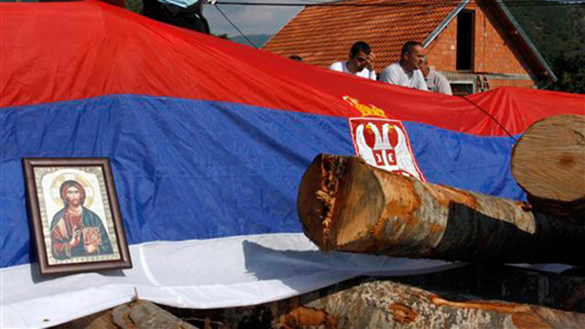 An icon and Serbian flag cover a barricade on the road near the village of Zupce, northern Kosovo, Monday, Aug. 1, 2011. A NATO spokesman in Kosovo says the military alliance has started removing roadblocks put up by Serbs in the country's north during a week of violence that left one Kosovo policeman dead.