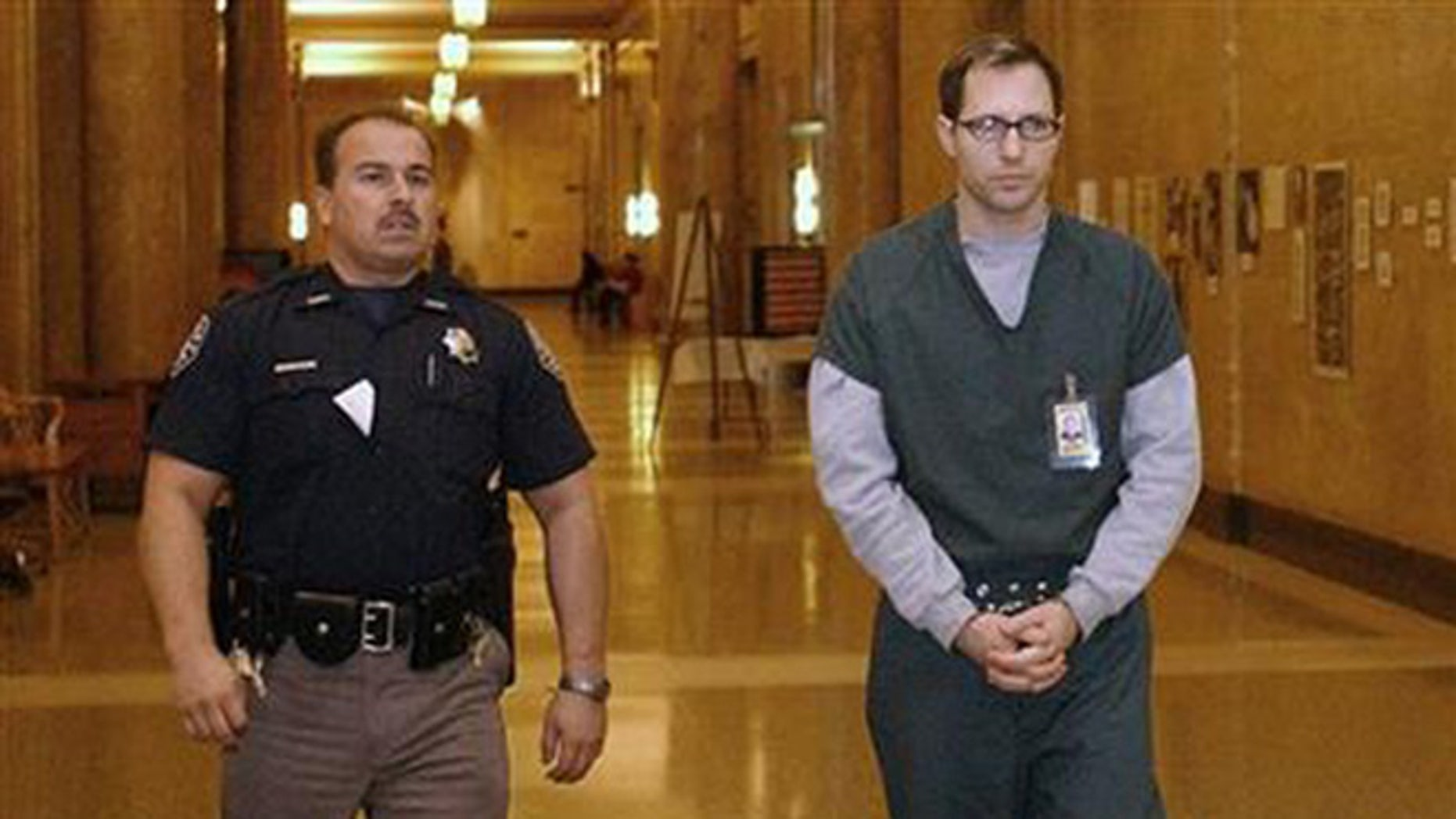 In this Feb. 21, 2002 file photo, Kurt Sonnenfeld, right, is led in handcuffs to a court for an appearance to face a first-degree murder charge in the death of his wife Nancy Sonnenfeld, in Denver, Colorado. On Dec. 11, 2104, Argentina's Supreme Court ruled that Sonnenfeld, who took refuge in the South American country in 2003, can be extradited to the U.S. to face charges that he killed his wife. Sonnenfeld had been a cameraman for the Federal Emergency Management Agency at the World Trade Center after the Sept. 11, 2001, terrorist attacks and claimed he had video footage indicating the government knew the attacks would happen. He claimed that his wife, who was found dead in their home on Jan. 1, 2002, had killed herself and that prosecutors framed him for her death to silence him, allegations that Denver's district attorney's office has denied. (AP Photo/The Denver Post, John Prieto, File)