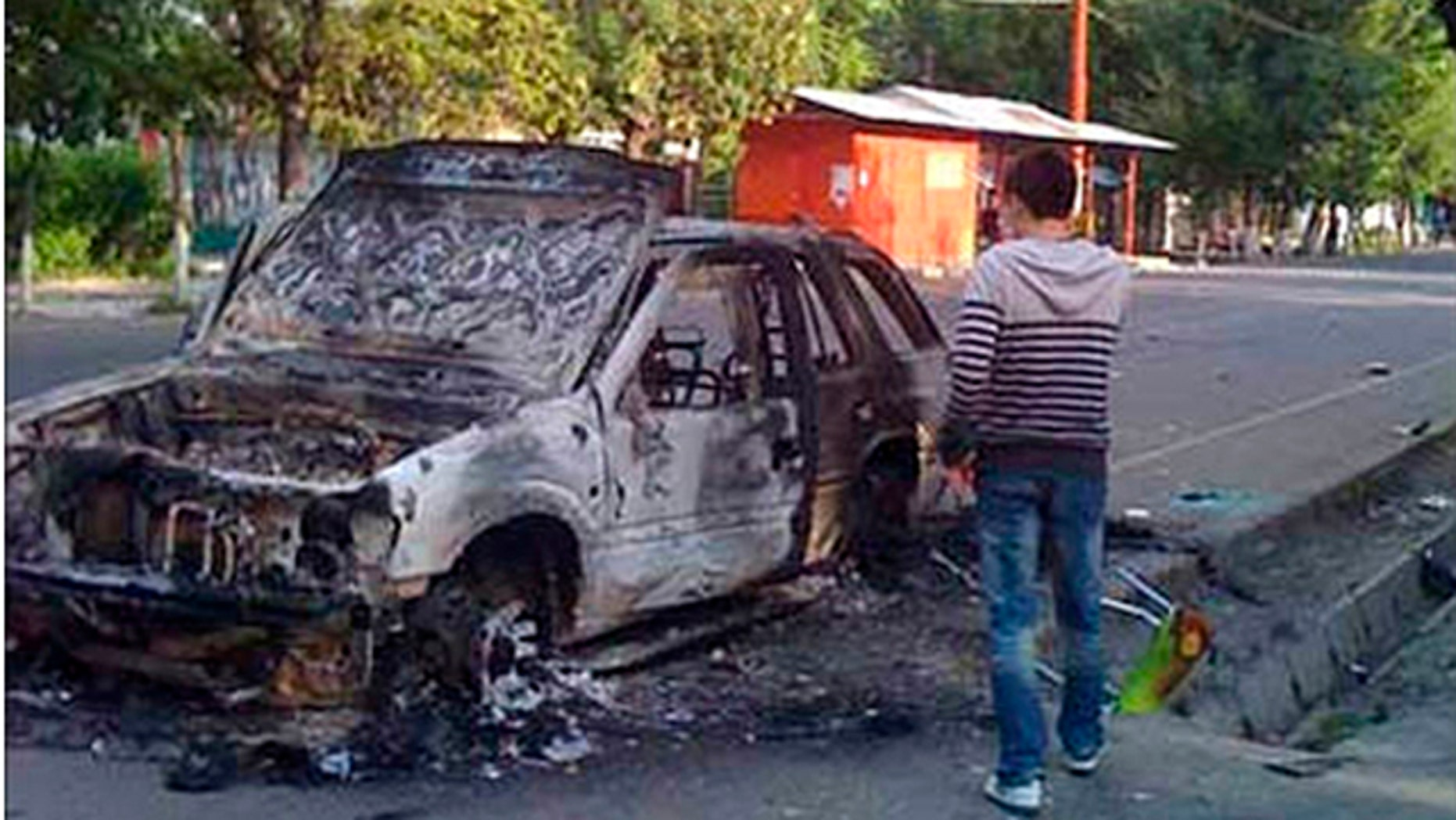 June 11: In this photo released by fergana.ru, a man examines a burnt car in Kyrgyzstan's second-largest city of Osh. (AP)