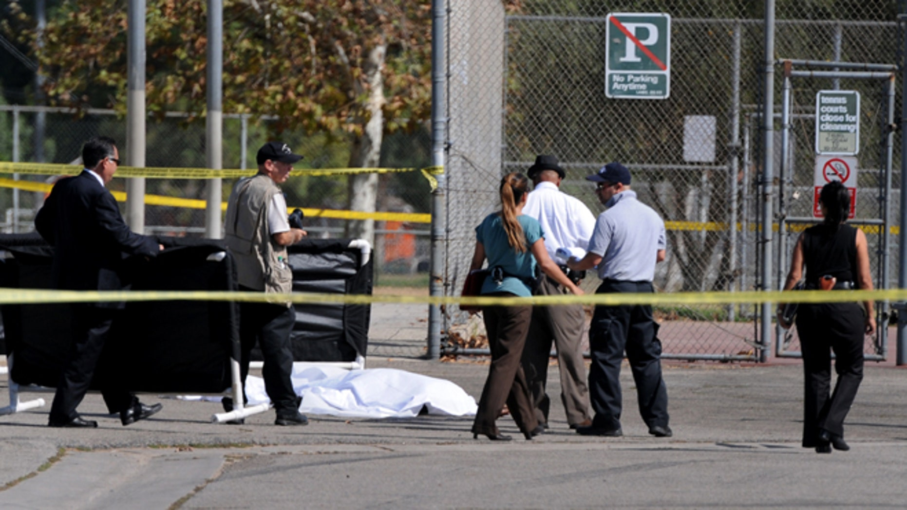 Los Angeles Police Department officers investigate the scene of a shooting Sunday, Aug. 24, 2014, where one person was killed near the 14400 block of Polk Street in Sylmar, Calif.  Describing what they called a major public threat, Los Angeles police said they are seeking clues to three separate shootings in the Northeast San Fernando Valley that left three people dead and four others injured early Sunday morning and appear to be connected. A suspect in the shootings was taken into custody by SWAT officers Sunday night after holing up inside a house in the Sylmar neighborhood for about an hour, Capt. William Hayes said.  (AP Photo/Los Angeles Daily News, Dean Musgrove)