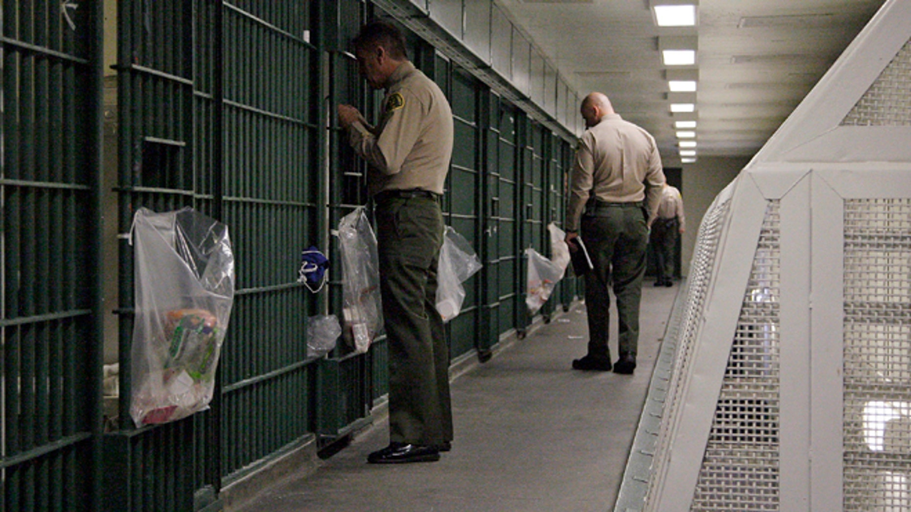 "FILE - In this Oct. 3, 2012, file photo, Los Angeles County Sheriff's deputies inspect a cell block at the Men's Central Jail in downtown Los Angeles. Federal officials say 18 current and former Los Angeles County sheriff's deputies saw themselves as being ""above the law,"" engaging in corruption and civil rights abuses that included beating inmates and visitors, falsifying reports, and trying to block an FBI probe of the nation's largest jail system. (AP Photo/Reed Saxon, File)"