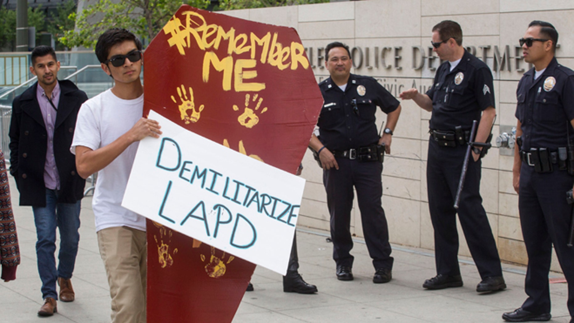 LOS ANGELES, CA - APRIL 7:  A demonstrator carrying a makeshift coffin walks past the Los Angeles Police Department Headquarters on April 7, 2015 in Los Angeles, California. The 'Remember Me' march was organized in downtown L.A. for people who have been killed by law enforcement. (Photo by Ringo Chiu/Getty Images)