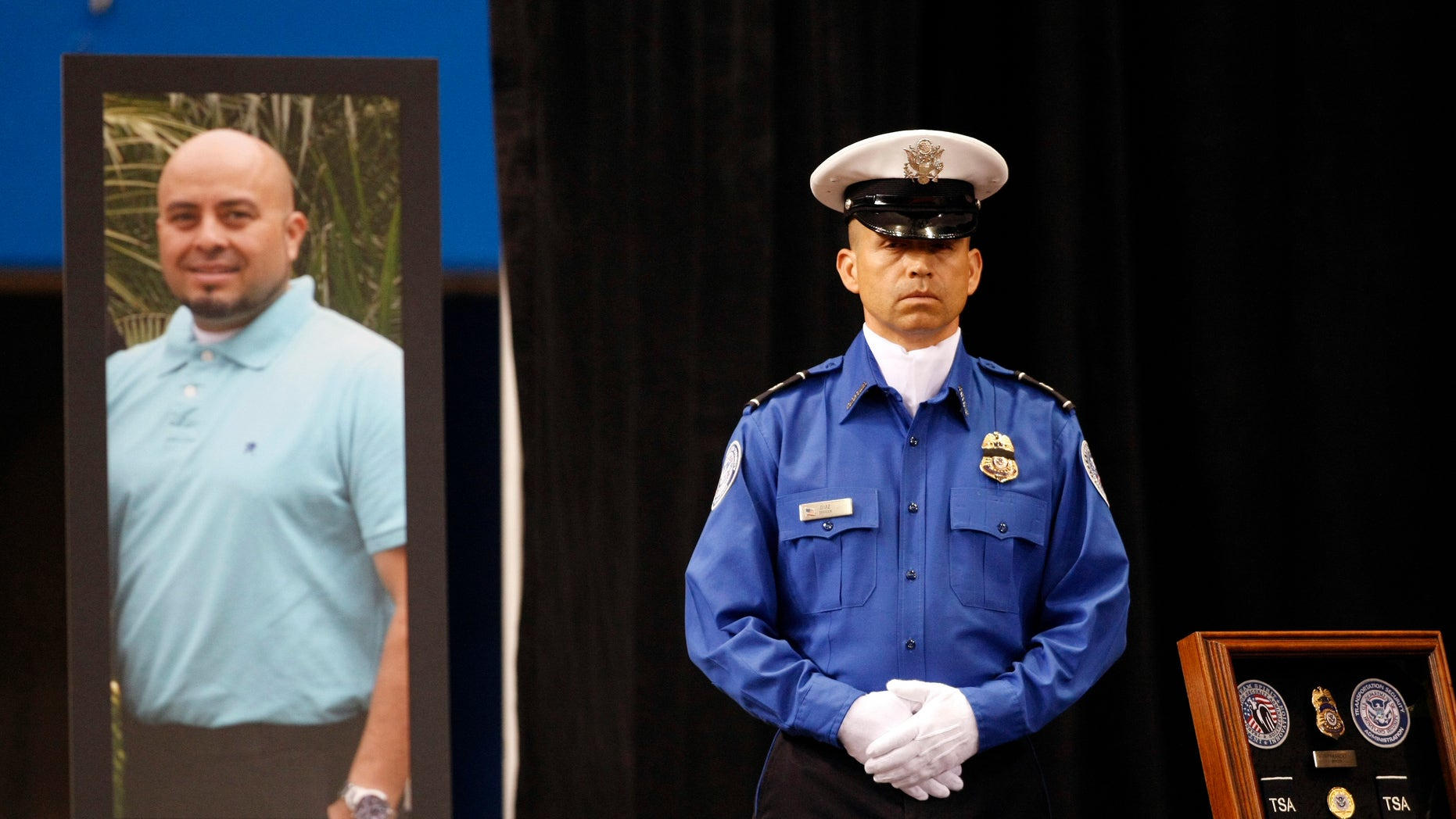 A TSA officer standS in front of a portrait of slain TSA officer Gerardo Hernandez during his public memorial at the Los Angeles Sports Arena, Tuesday, Nov. 12, 2013.