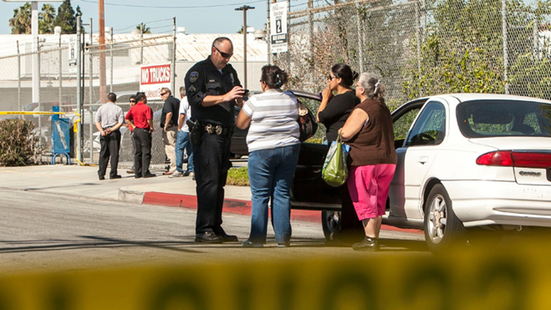 Oct. 24, 2012: Police investigators talk to people across the street from a family-owned business, United States Fire Protection Services, in Downey, Calif.