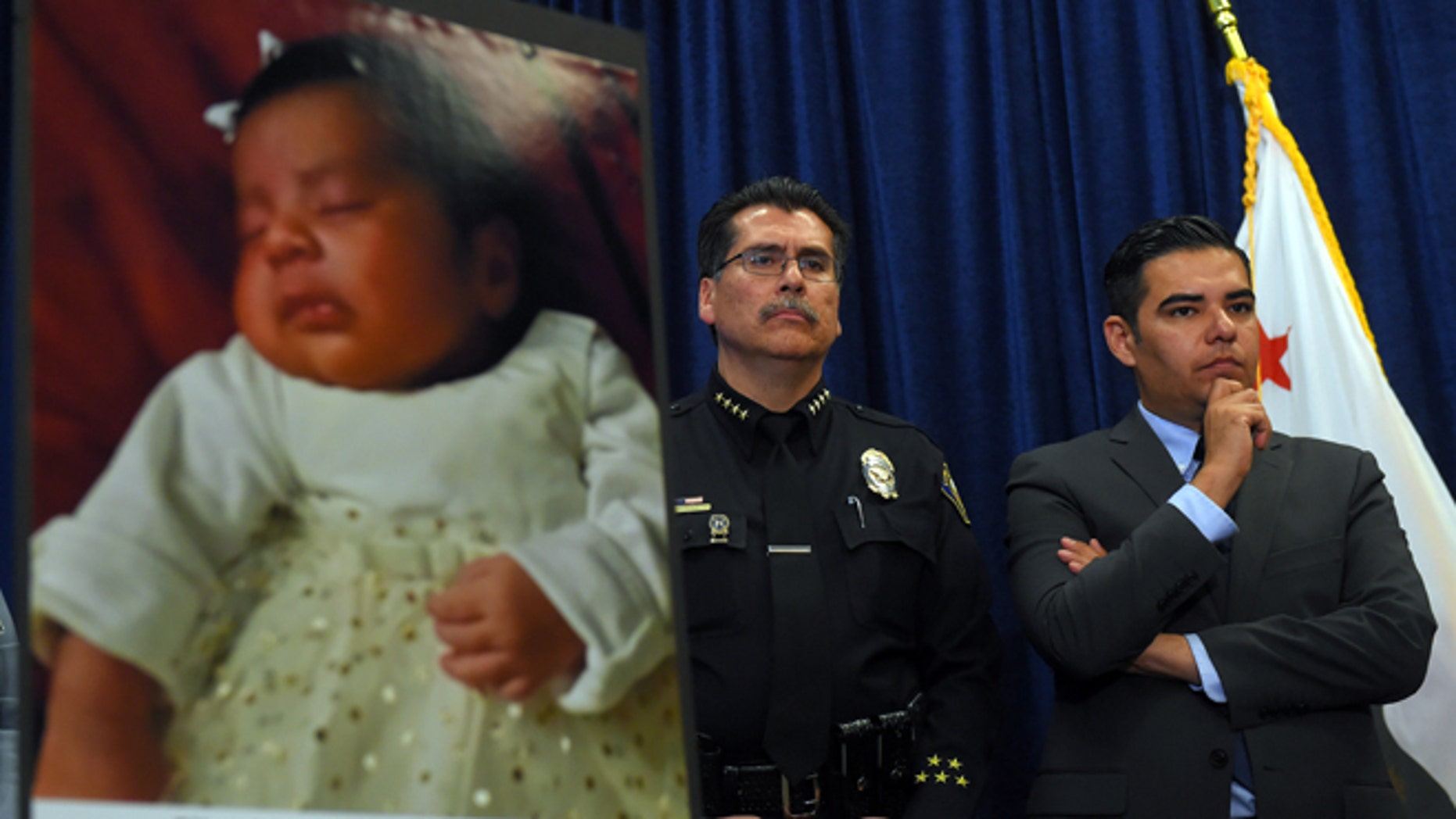 Long Beach Police Chief Robert Luna, left, and Mayor Robert Garcia stand during a news conference in Long Beach, Calif., Wednesday, March 25, 2015. Southern California authorities have arrested four people in a plot to kidnap two newborn babies. The plot ended with the death of a 3-week-old girl and the shooting and beating of the childrens mothers, police said Wednesday. At left is an image of baby Eliza Delacruz, who was snatched Jan. 3, 2015, in Long Beach by a gunman who wounded her parents and uncle, Luna said. Her body was found the next day in a trash bin near the Mexican border. (AP Photo/The Daily Breeze, Scott Varley)  MAGS OUT; NO SALES