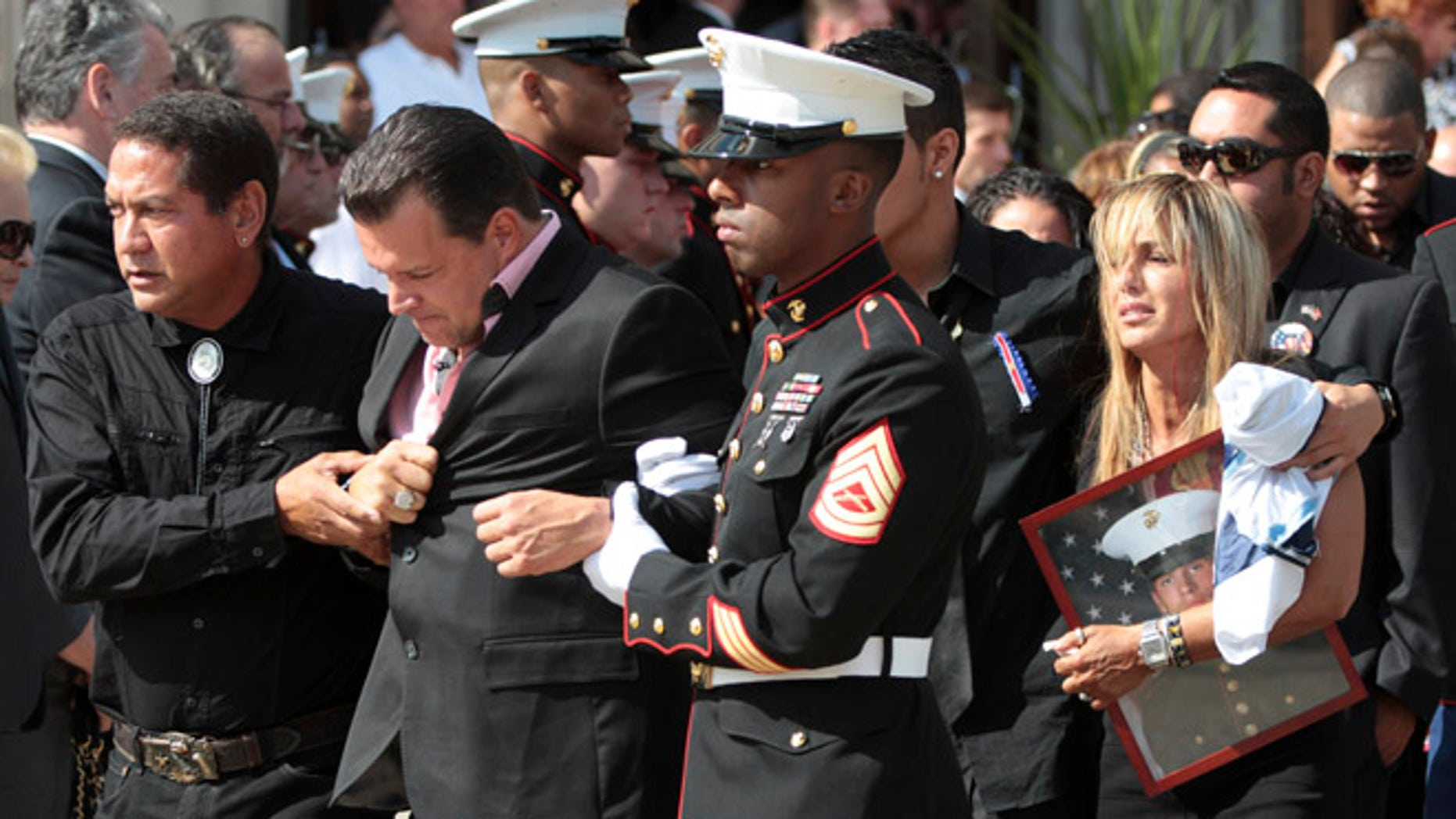 Aug. 18, 2012: Lance Cpl. GregBuckleyJr.'s father Greg, foreground and mother Marina are escorted from St. Agnes Cathedral after his funeral Mass in Rockville Center, N.Y..