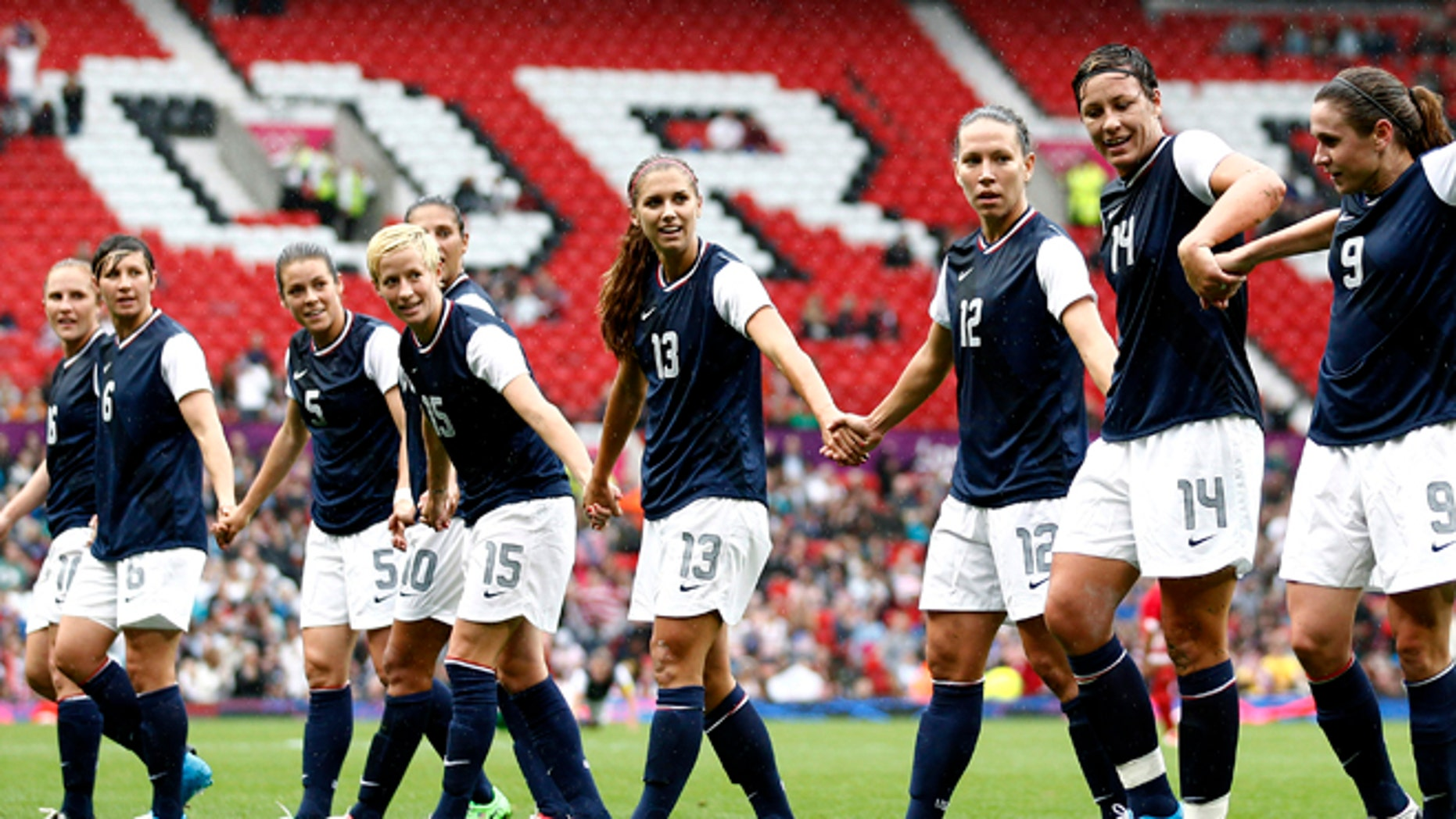 July 31, 2012: United States' Abby Wambach (14) celebrates with teammates after scoring against North Korea during their group G women's soccer match at the London 2012 Summer Olympics, at Old Trafford Stadium in Manchester, England.