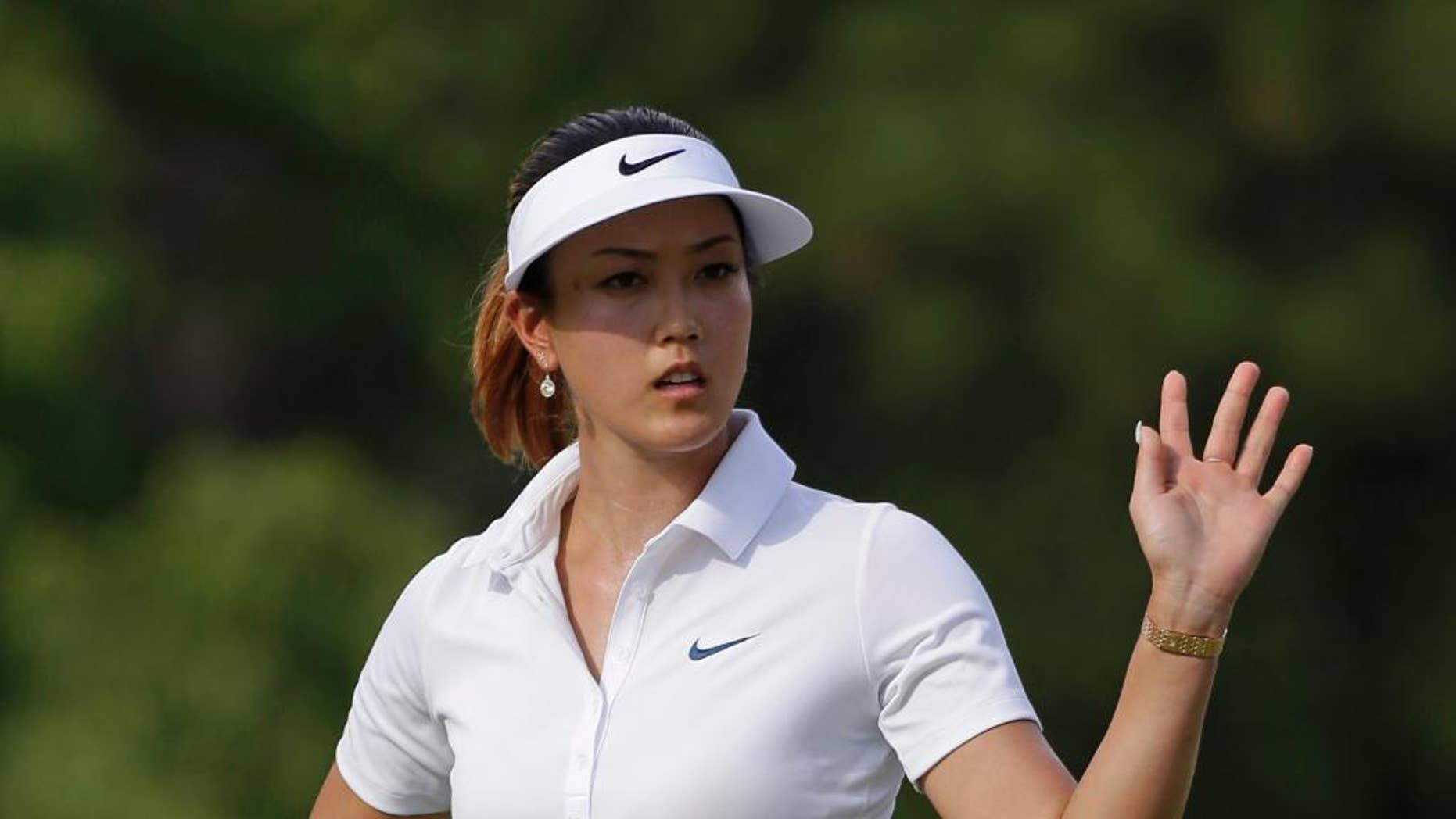 Michelle Wie waves after making a putt on the 14th hole during the first round of the LPGA U.S. Women's Open golf tournament in Pinehurst, N.C., Thursday, June 19, 2014. (AP Photo/Bob Leverone)