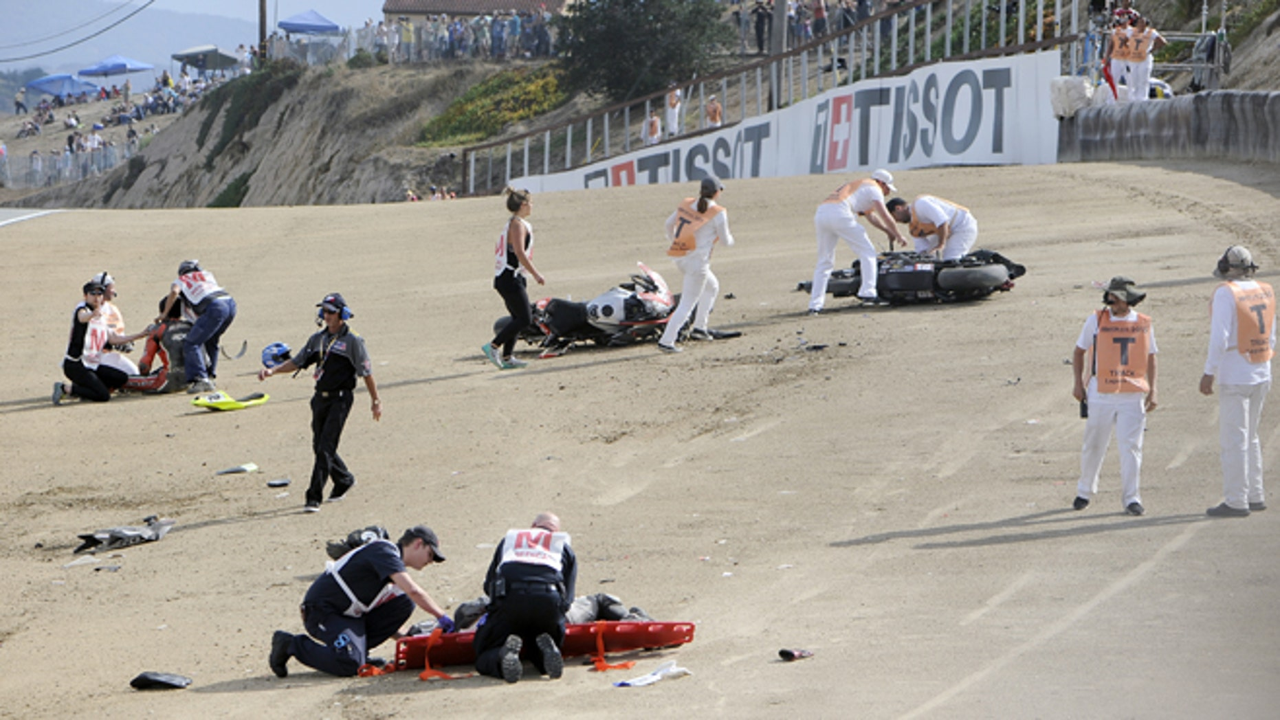 In this Sunday, July 19, 2015, photo, medical and track personnel attend to downed riders after a chain reaction crash on the first lap of a World Superbike race at Mazda Raceway at Laguna Seca in Monterey, Calif. Two Spanish racers were killed in the crash. (Nic Coury/Monterey County Weekly via AP)