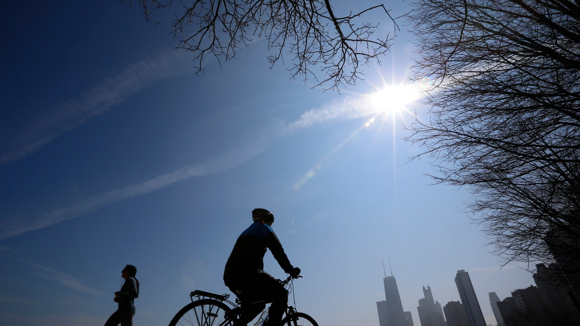 A jogger and a cyclist make their way around Lake Michigan in Chicago, March 21, 2014. (REUTERS/Jim Young)