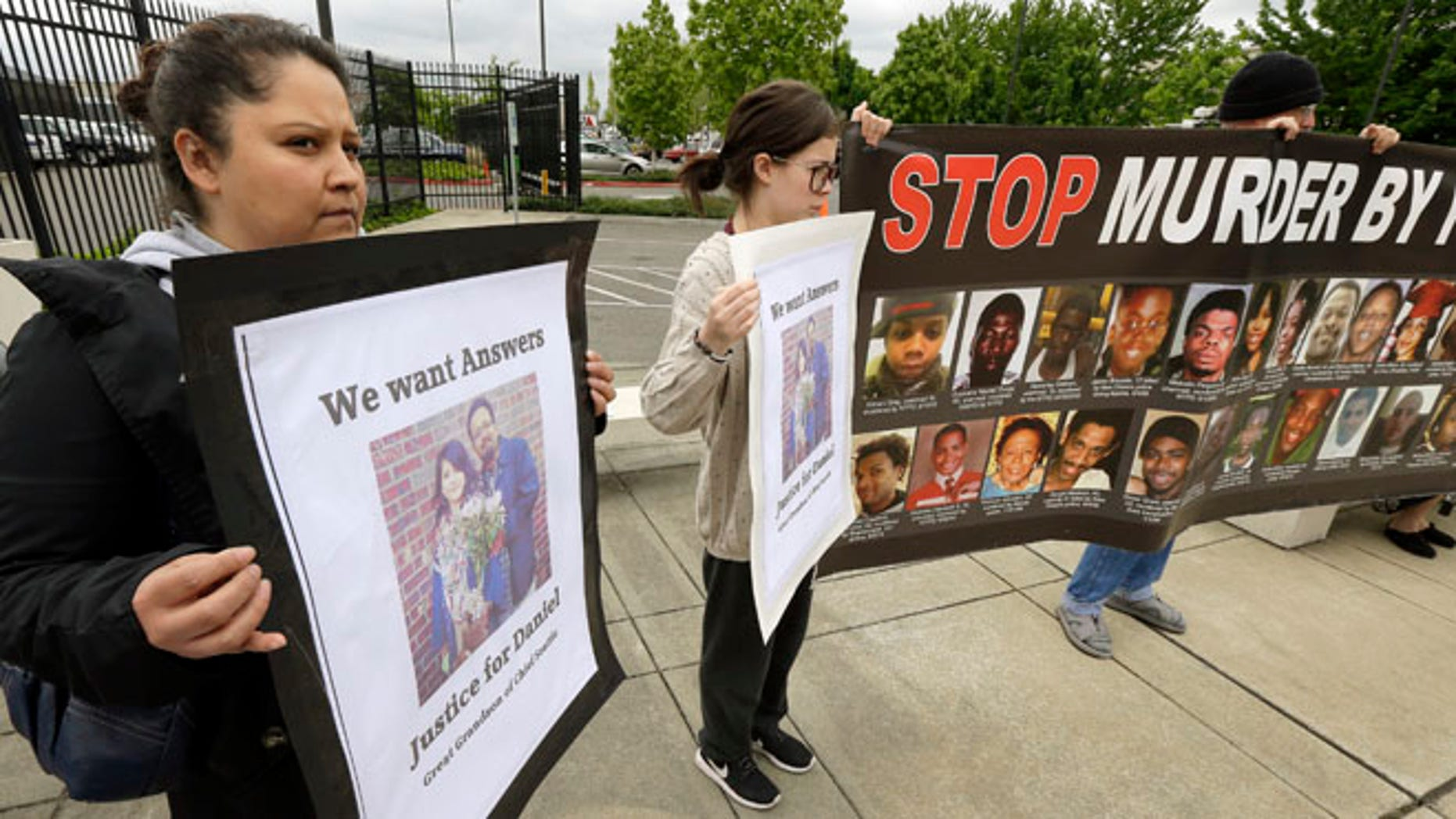 Lanna Covarrubias, left, the sister of Daniel Covarrubias, holds a sign Monday, May 11, 2015, as she stands with supporters outside police headquarters in Lakewood, Wash. The interim police chief in Lakewood says officers shot and killed Daniel Covarrubias in a lumber yard last month because he pointed a cell phone at them as though it were a gun. (AP Photo/Ted S. Warren)