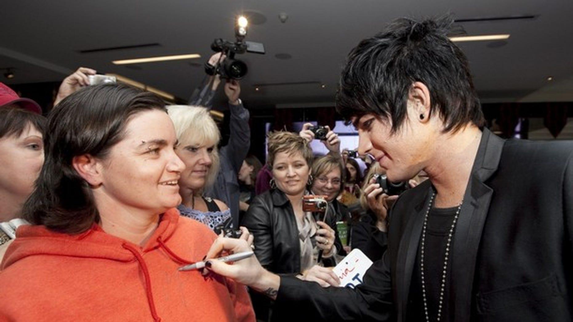 Singer Adam Lambert autographs a fan's sweatshirt.