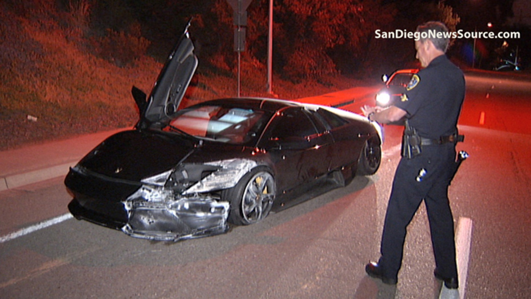 Police inspect the damage to a banged up 2008 Lamborghini on the side of La Jolla Village Drive.