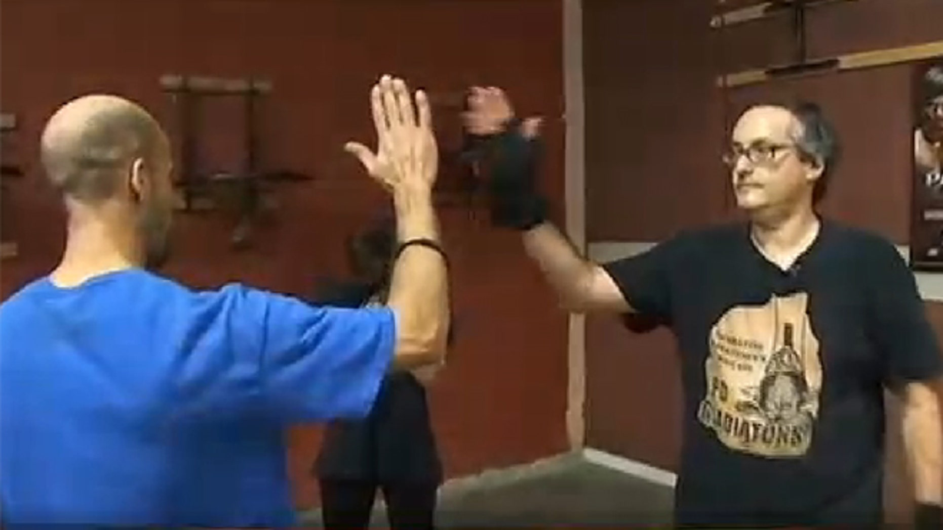 Larry Kahn high-fives his instructor after a boxing work out.