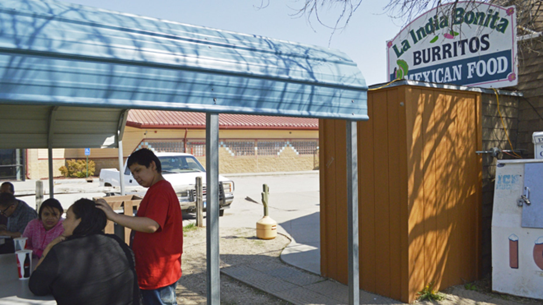 FILE - In this May 1, 2015 file photo, customers eat outside La India Bonita Mexican Restaurant in Kyle, S.D., on the Pine Ridge Indian Reservation. The population growth of U.S. Latinos is slowing thanks to lower immigration and declining birthrates, although states like North Dakota, South Dakota, and Tennessee are seeing Latino population spikes, according to a Pew Research Center study released Thursday, Sept. 8, 2016. (AP Photo/Russell Contreras, File)