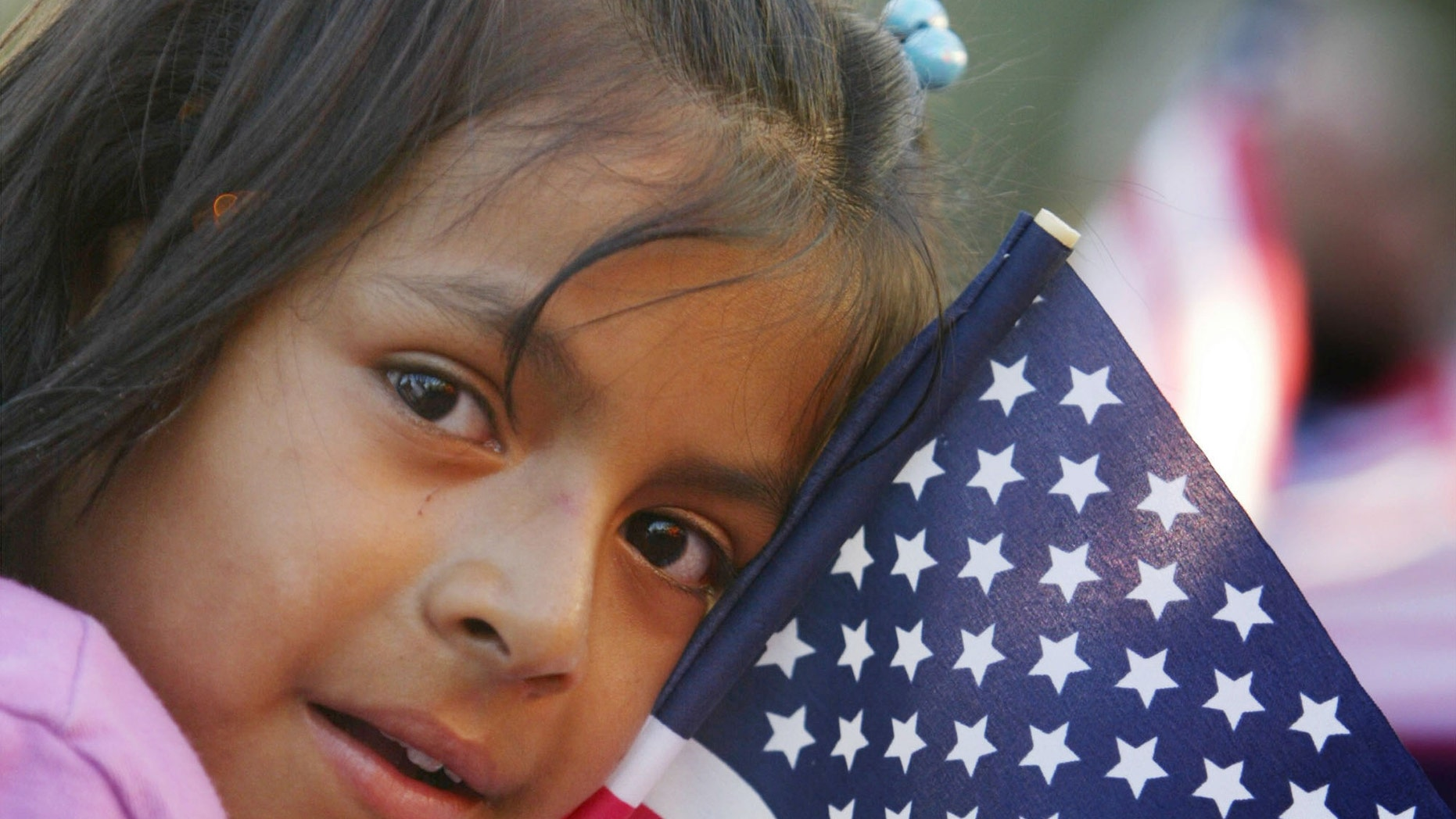 LOS ANGELES - SEPTEMBER 5:  A Latina girl clutches an American flag while waiting to see California Governor Gray Davis sign the controversial SB 60 into law,, allowing undocumented immigrants to get a California driver's license September 5, 2003 in Los Angeles, California. Critics claim that Davis reversed his position on the bill to gain Latino votes in the October 7 recall election.  (Photo by David McNew/Getty Images)