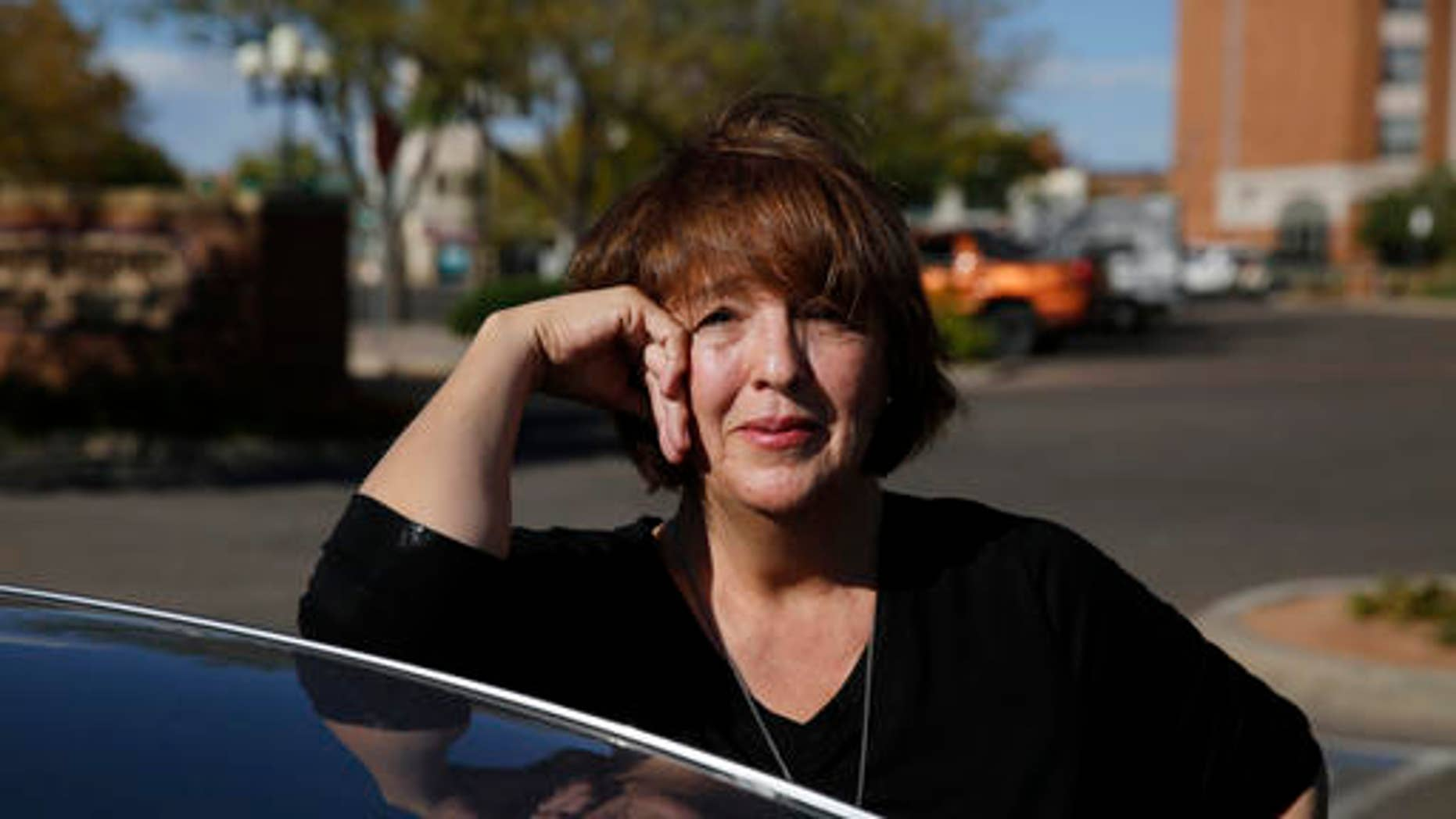 In this Oct. 4, 2016 photo, Donald Trump supporter Mary Celeste Madrid stands by her car, in Pueblo, Colo. A longtime Democrat and Obama voter who changed her registration to Republican last year over the GOP's support for gun rights and opposition to abortion, Madrid says she's also had to endure family battles over her support for Trump. (AP Photo/Brennan Linsley)