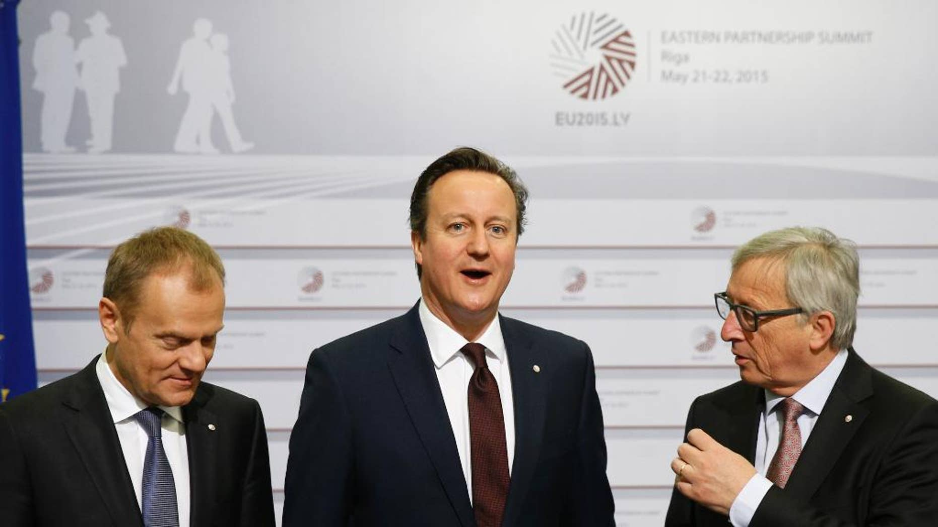 British Prime Minister David Cameron, center, stands with European Commission President Jean-Claude Juncker, right, and European Council President Donald Tusk during arrivals at the Eastern Partnership summit in Riga, on Friday, May 22, 2015. EU leaders gather for a second day of meetings with six post-communist nations to discuss various issues, including enlargement, the economy and Ukraine. (AP Photo/Mindaugas Kulbis)
