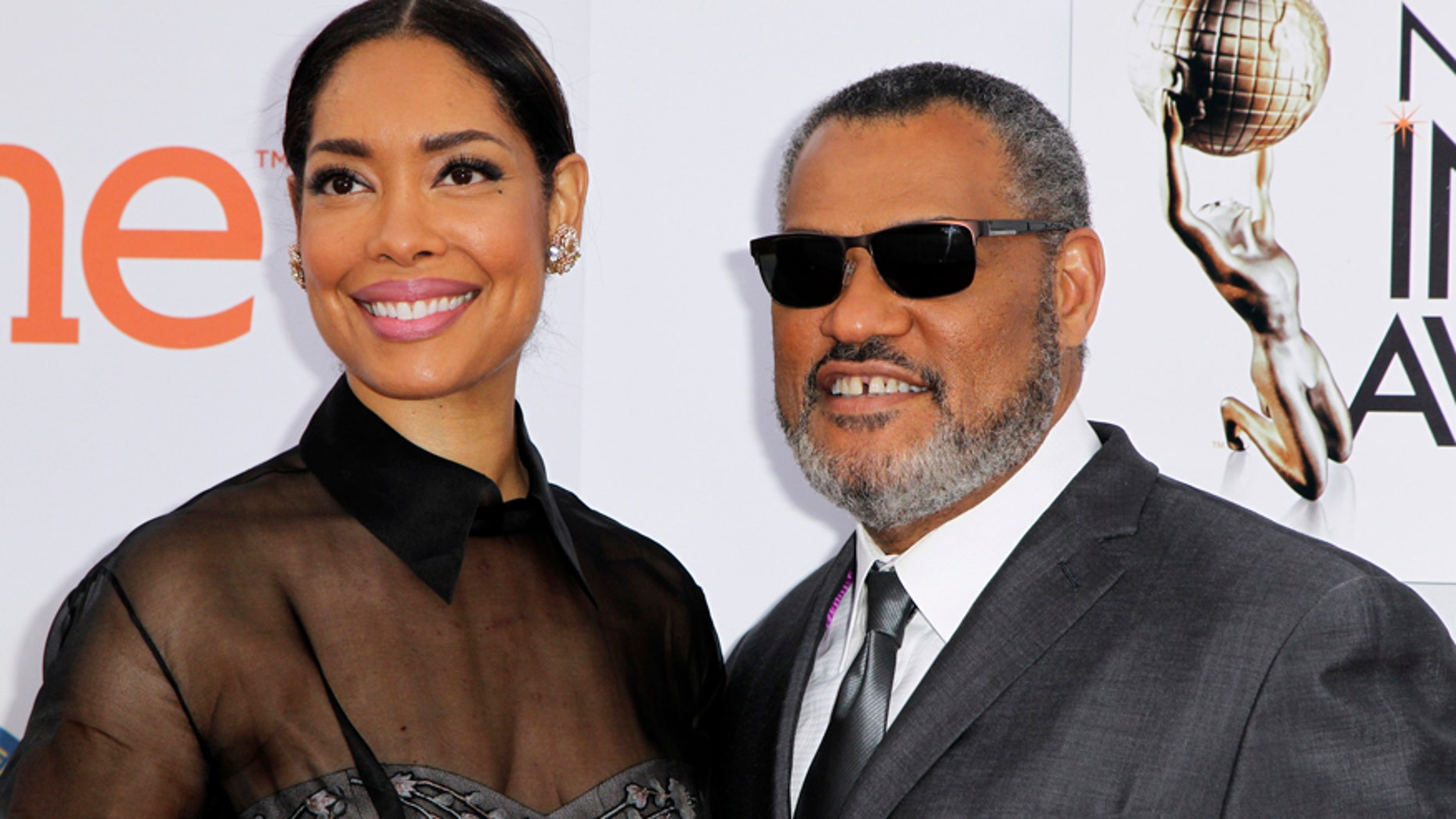 Actor Laurence Fishburne and wife, Gina Torres, arrive at the 46th NAACP Image Awards in Pasadena, California February 6, 2015.