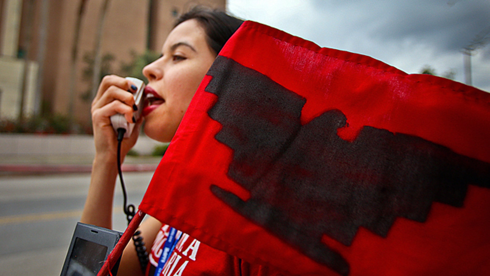 "Yvette Salinas, with L.U.P.E chants ""Education not Deportation"" into a megaphone on Thursday, March, 19, 2015 outside of the federal courthouse in Brownsville, Texas.   The Justice Department might face sanctions if a federal judge determines its attorneys misled him about whether part of President Barack Obama's executive action on immigration was implemented prior to it being put on hold by the judge. U.S. District Judge Andrew Hanen last month halted Obama's plan. The president's plan would spare from deportation up to 5 million people in the U.S. illegally. (AP Photo/The Brownsville Herald, Yvette Vela)"