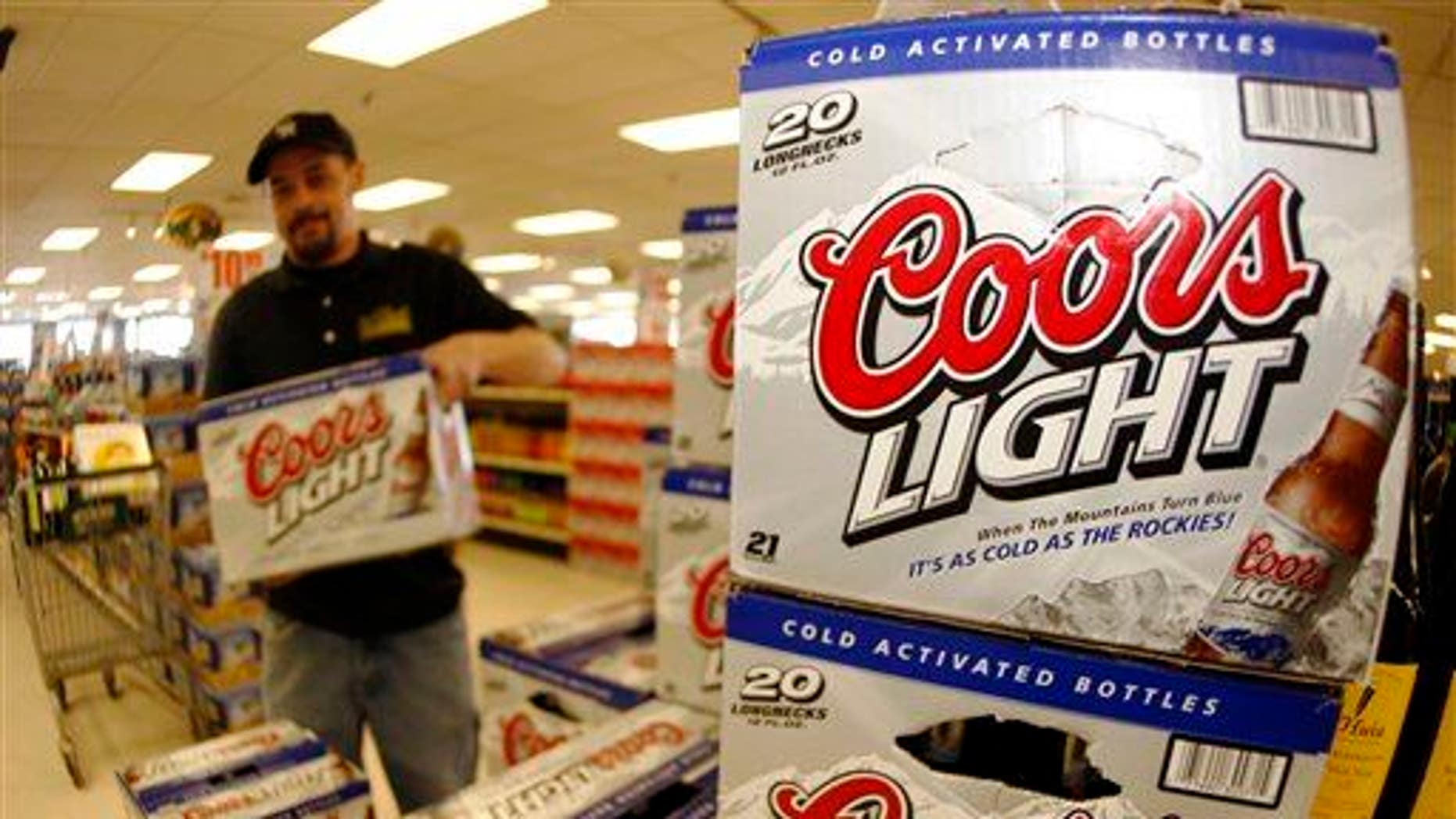 Eli Hughes stocks cases of Coors Light in the Applejack Liquor Store in the west Denver suburb of Wheat Ridge, Colo.