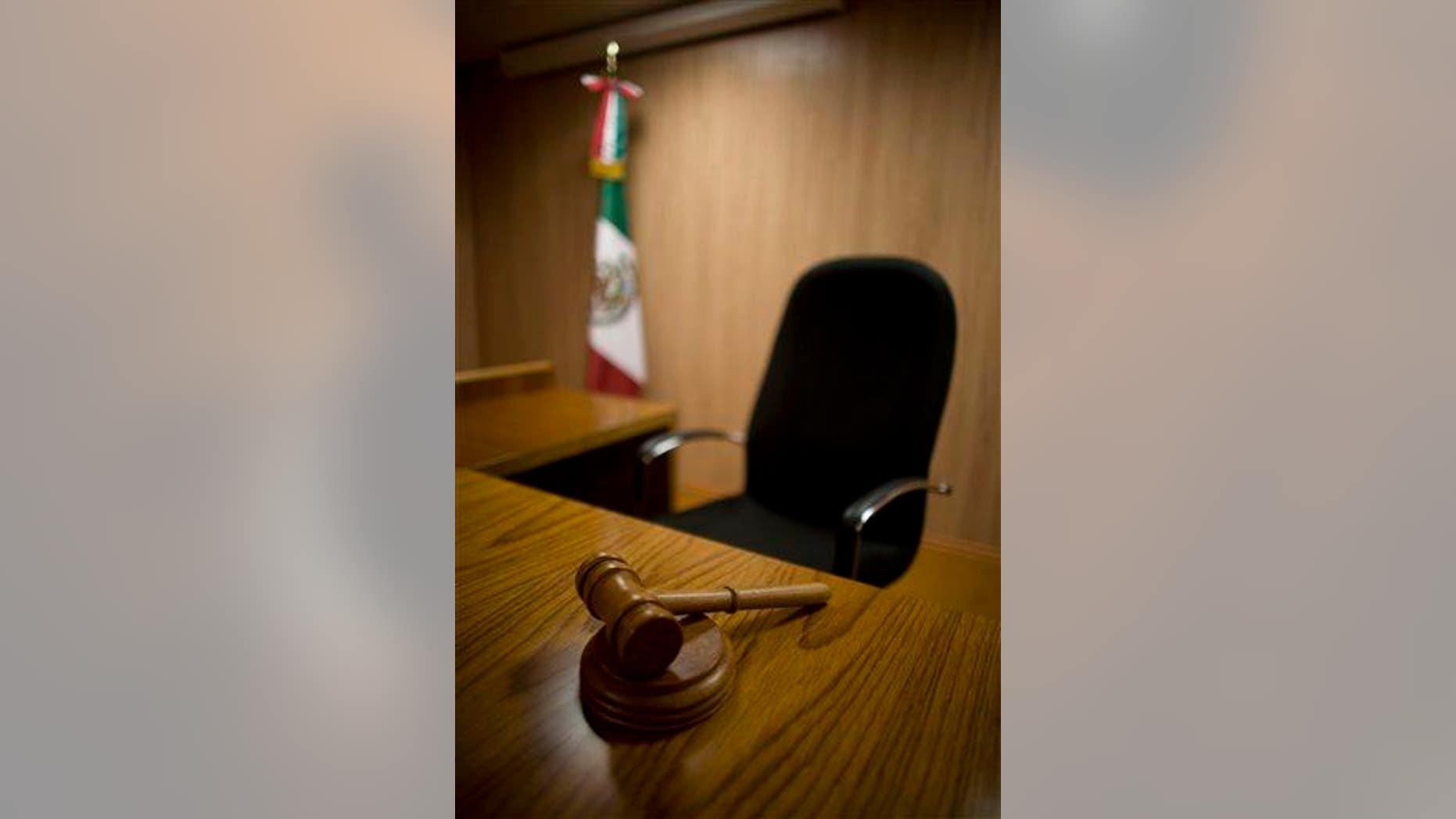 FILE -  In this July 12, 2008 file photo, a gavel rests on the table of a model court room at Mexico's National Institute of Penal Sciences in Mexico City. The model courtroom has been used by students to prepare for the new legal system that will replace its closed proceedings with public oral trials in which suspects are presumed innocent, legal authorities can be held more accountable and equal justice is promised to all. Yet the decision of three Chihuahua state judges, under the new open oral trial system, to absolve the main suspect in the 2008 murder of a 16-year-old girl has put the country's U.S.-backed judicial reform on trial. (AP Photo/Dario Lopez-Mills, File)