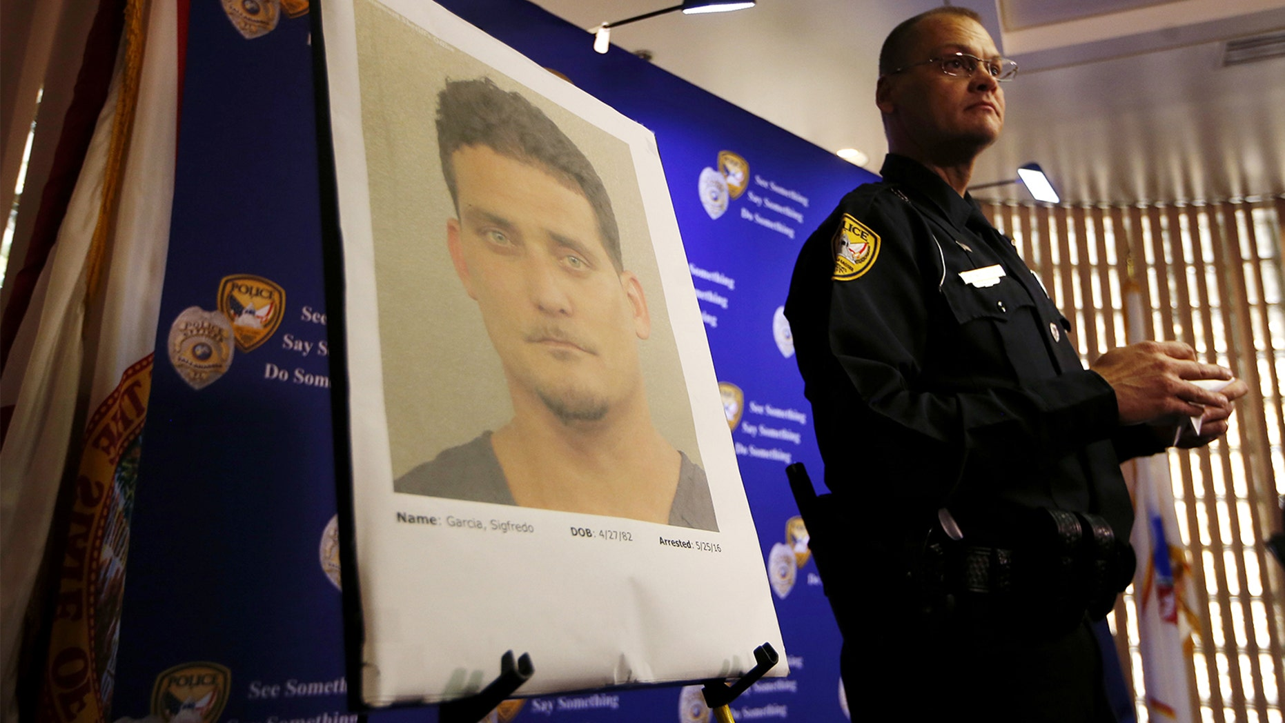 Tallahassee Police Department Public information officer David Northway reveals an image of Sigfredo Garcia, 34, during a press conference in Tallahassee, Fla., Thursday, May 26, 2016. Garcia is wanted for the murder of Florida State University law professor Dan Markel. Markel was killed in his Tallahassee home in July 2014. (Joe Rondone/Tallahassee Democrat via AP)