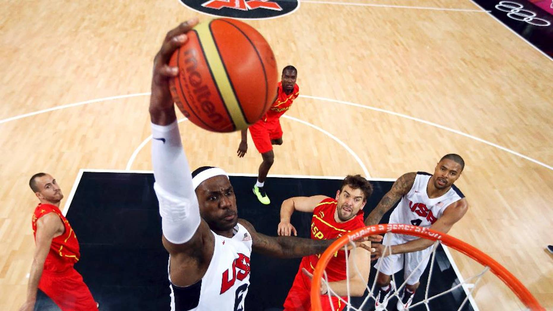 """FILE - In this Aug. 12, 2012, file photo, United States' LeBron James (6) dunks against Spain during the men's gold medal basketball game at the 2012 Summer Olympics in London. James said Monday, Sept. 29, 2014, following the Cavaliers' practice that he's """"nowhere near"""" deciding if he'll again play for Team USA in two years for the 2016 Olympics. (AP Photo/Christian Petersen, Pool, File)"""