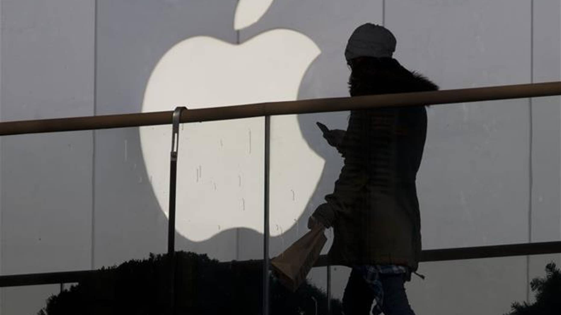 A woman walks past an Apple store in Beijing in this file photo. In dozens of leaked emails, women working at the company's headquarters in California complained of a sexism and gender harassment.
