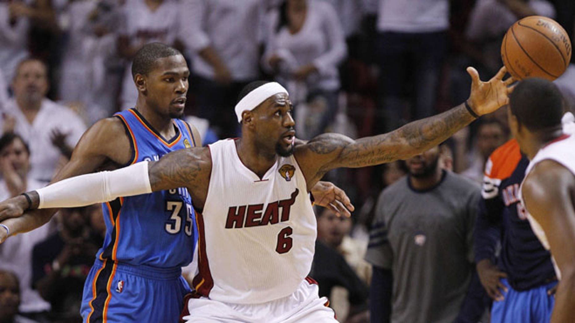 June 19, 2012: Miami Heat small forward LeBron James (6) reels in the ball as Oklahoma City Thunder small forward Kevin Durant (35) defends during the second half at Game 4 of the NBA Finals basketball series in Miami.