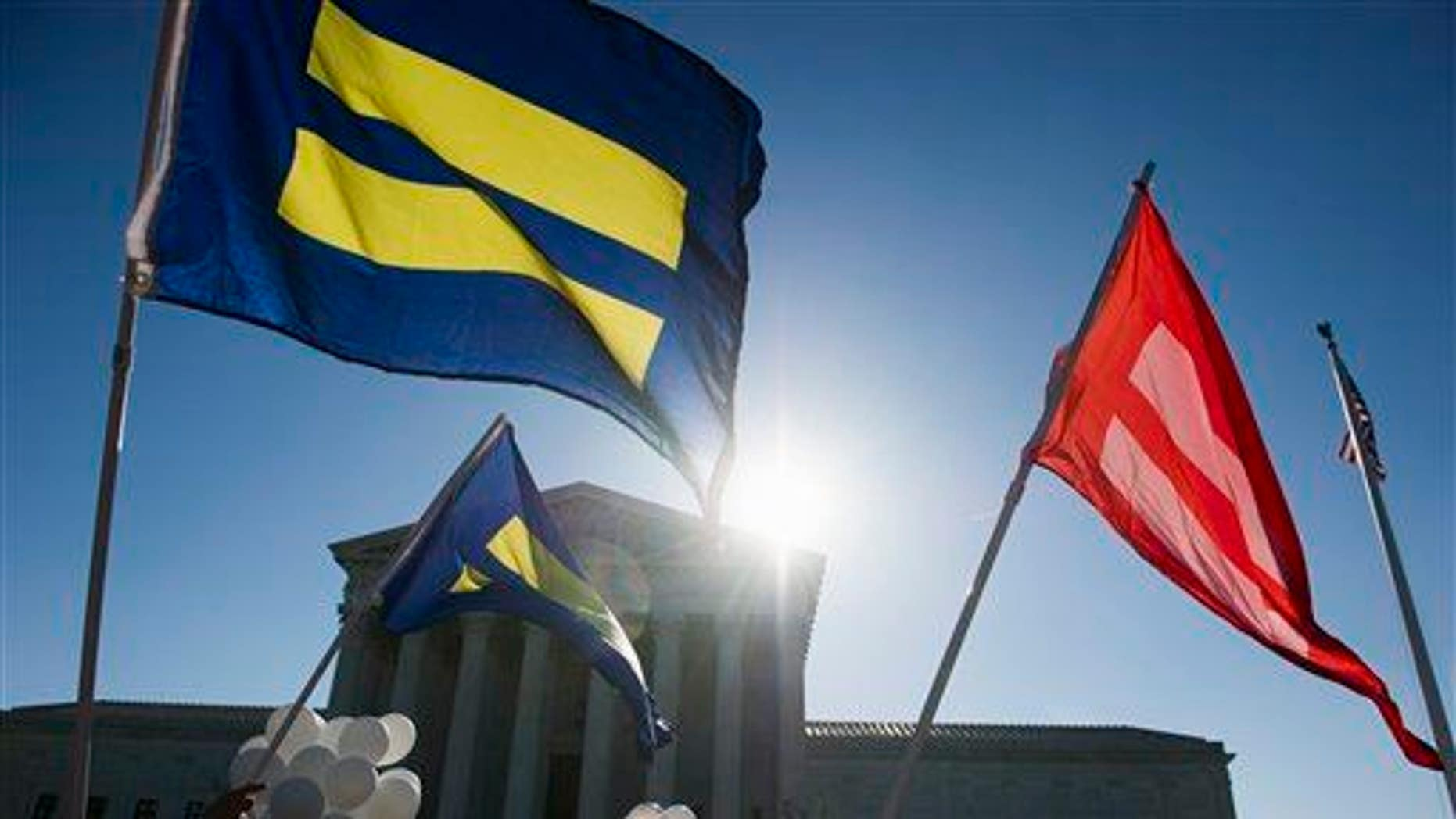 Equality flags fly in front of the Supreme Court in Washington, Tuesday, April 28, 2015
