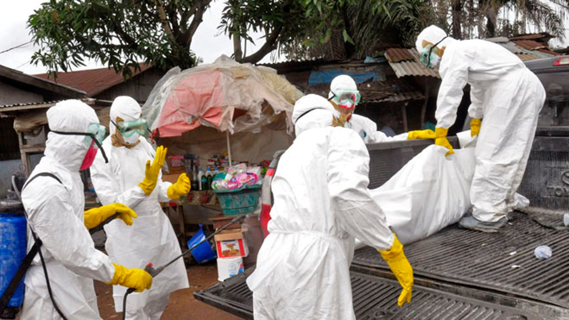Sept. 10, 2014: Health workers load the body of a woman they suspect died from the Ebola virus onto a truck in Monrovia, Liberia.